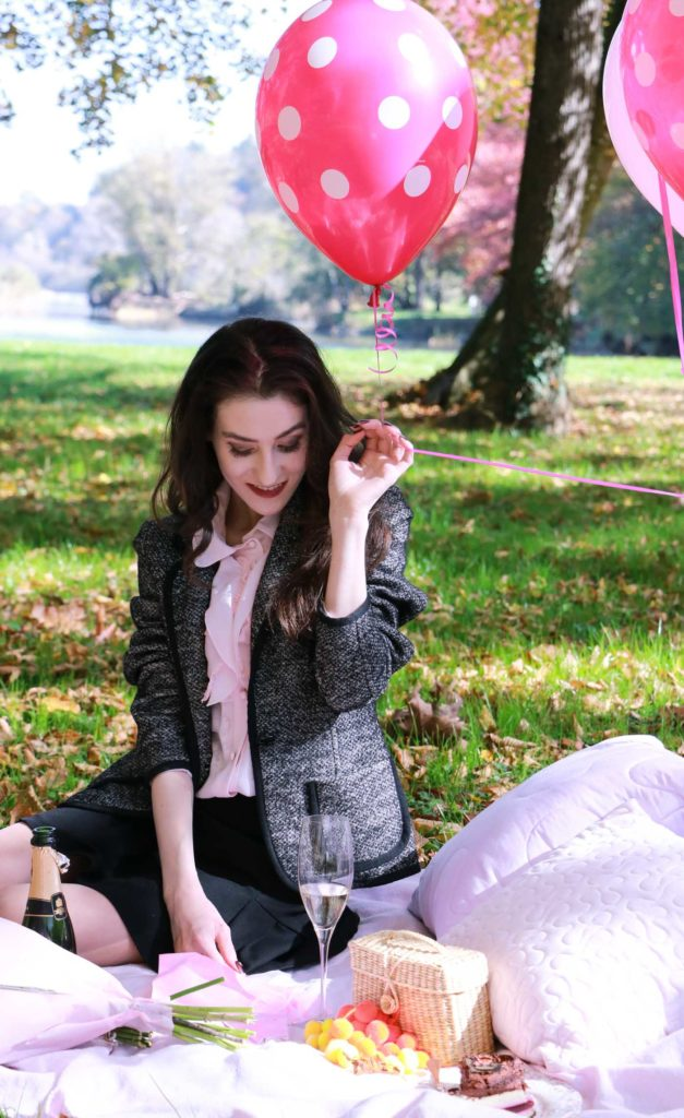 Fashion Blogger Veronika Lipar of Brunette from Wall Street sitting on a pink picnic blanket holding pink balloons