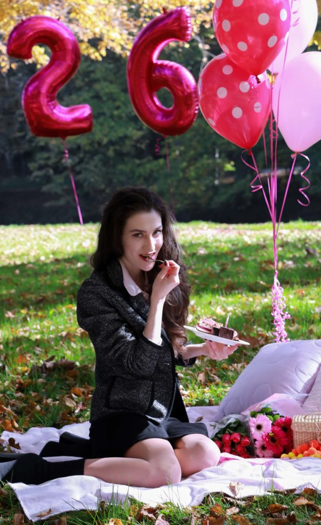 Fashion Blogger Veronika Lipar of Brunette from Wall Street wearing chic mini ruffled skirt, tweed jacket, romantic ruffled pink blouse and ankle booties while eating her birthday cake at fall picnic