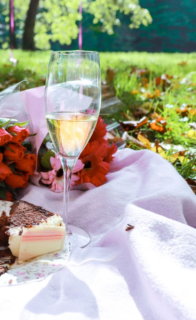 Glass of champagne, red roses, cake