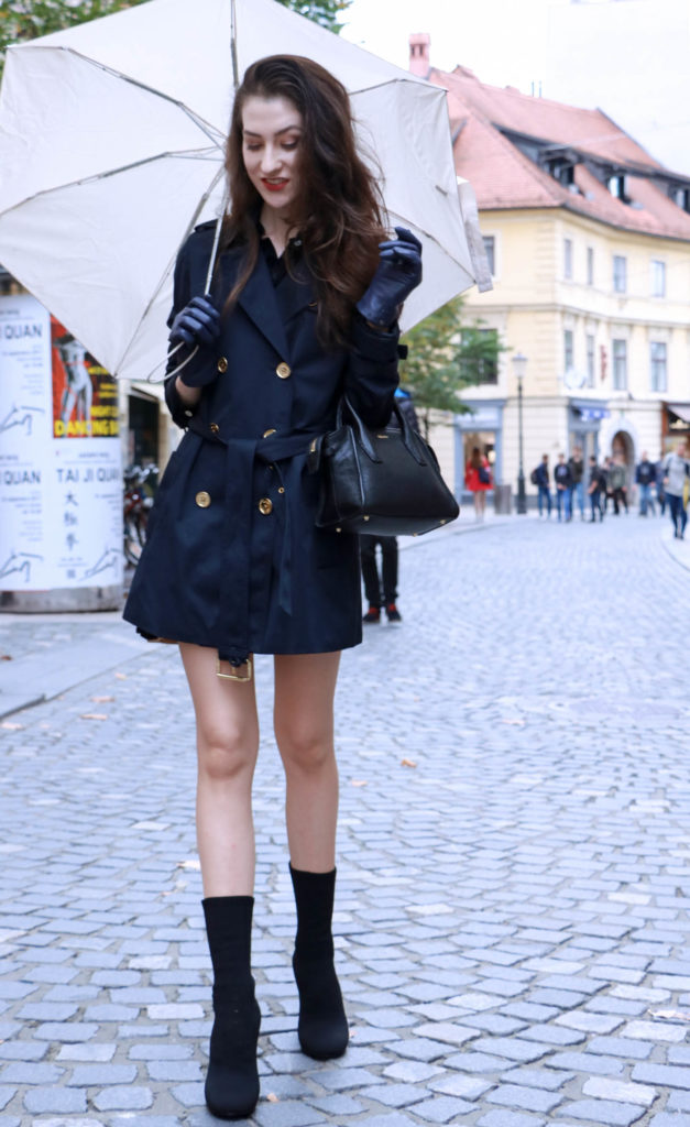 Fashion Blogger Veronika Lipar of Brunette from Wall Street dressed in blue trench coat and black sock booties in the rain