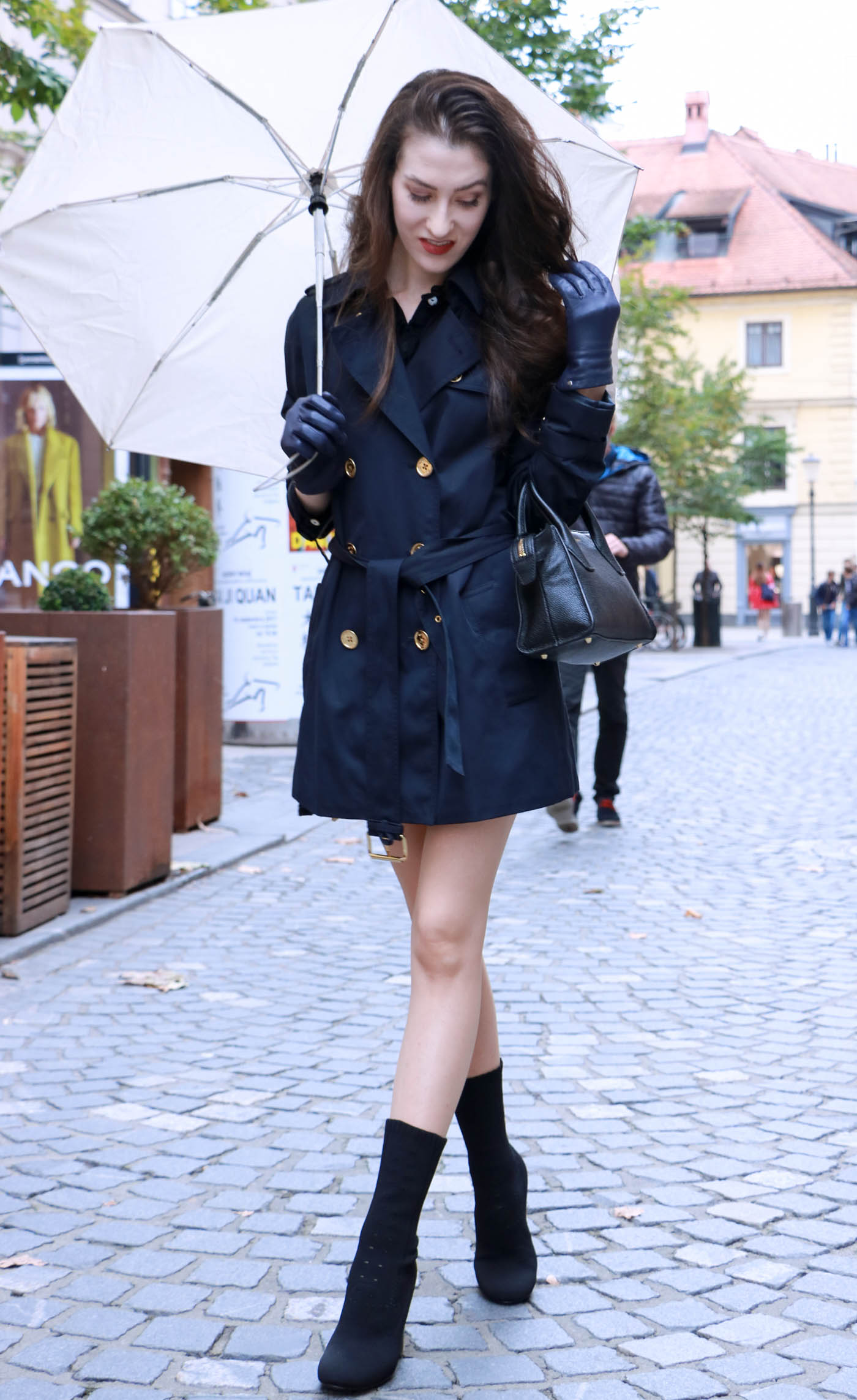 Fashion Blogger Veronika Lipar of Brunette from Wall Street wearing blue trench coat and ankle boots on a rainy day
