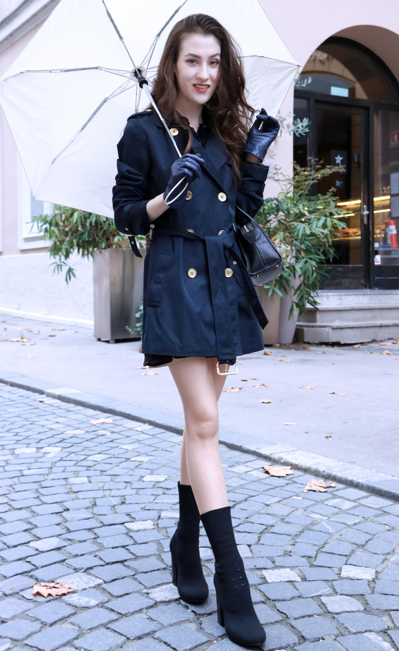 Fashion Blogger Veronika Lipar of Brunette from Wall Street dressed in blue trench coat and black sock booties this fall when it rains