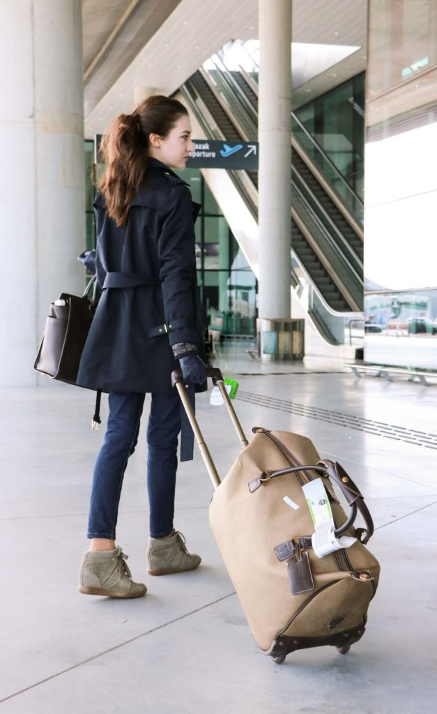 Fashion Blogger Veronika Lipar of Brunette from Wall Street wearing trench coat, oversized blazer and jeans on a flight to Paris
