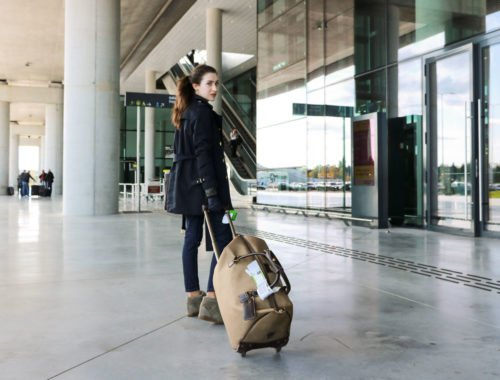 Fashion Blogger Veronika Lipar of Brunette from Wall Street wearing trench coat and jeans at the airport