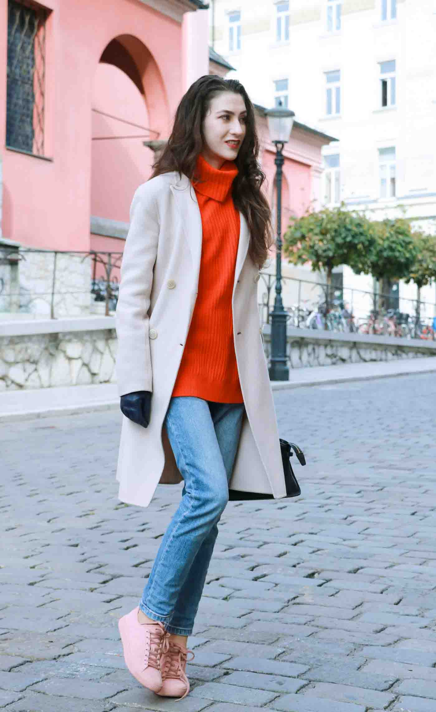 Fashion Blogger Veronika Lipar of Brunette from Wall wearing red Ganni turtleneck sweater, light blue jeans, dusty pink sneakers and Weekend Maxmara double breasted coat