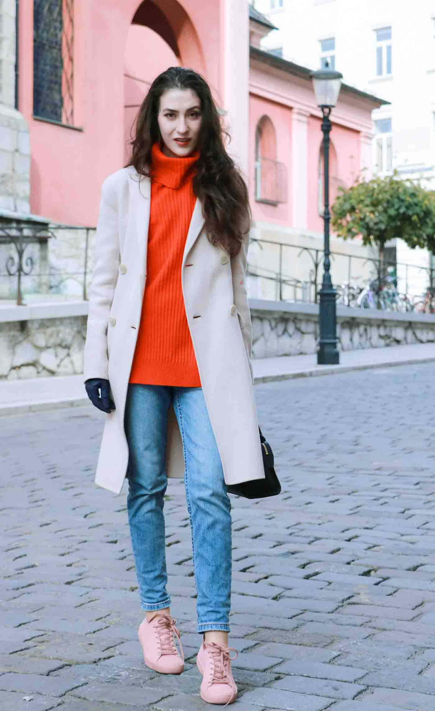 Fashion Blogger Veronika Lipar of Brunette from Wall wearing red Ganni turtleneck sweater, blue mom jeans, millennium pink sneakers and Weekend Maxmara white princess coat