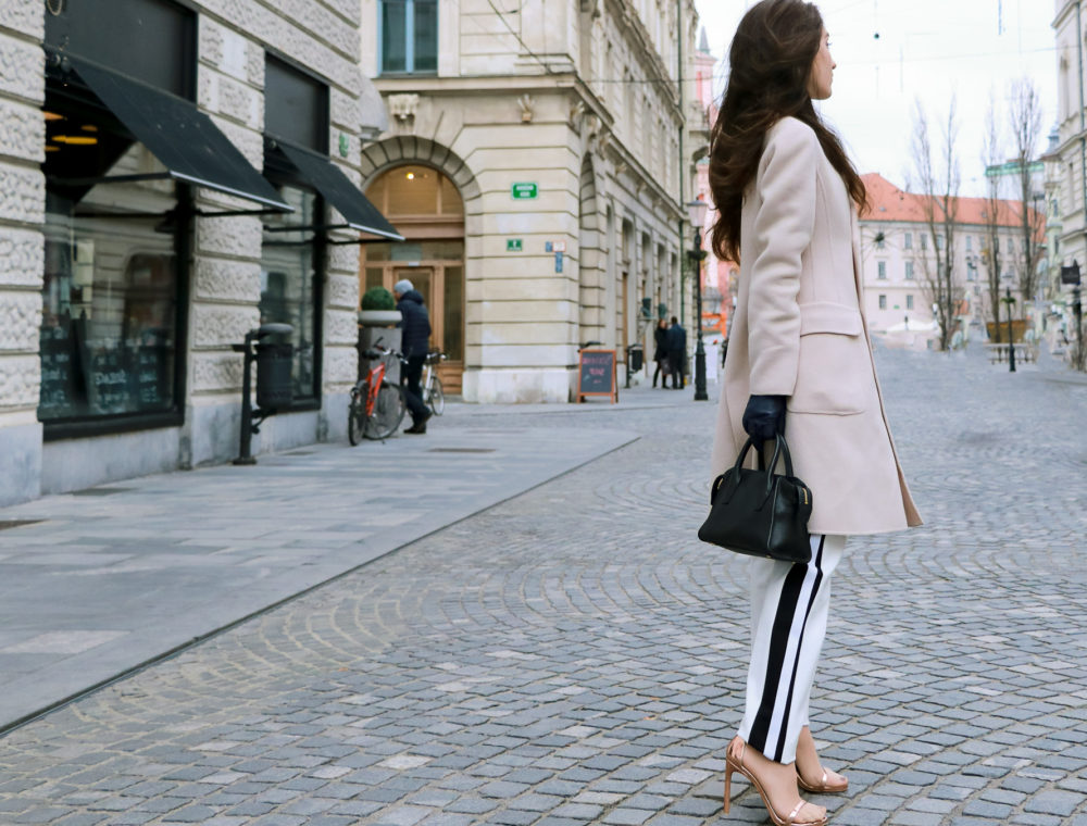 Fashion blogger Veronika Lipar of Brunette from Wall Street wearing white Escada track pants off-white Weekend Max Mara double breasted coat black top handle bag blue gloves Stuart Weitzman Nudistsong sandals in winter