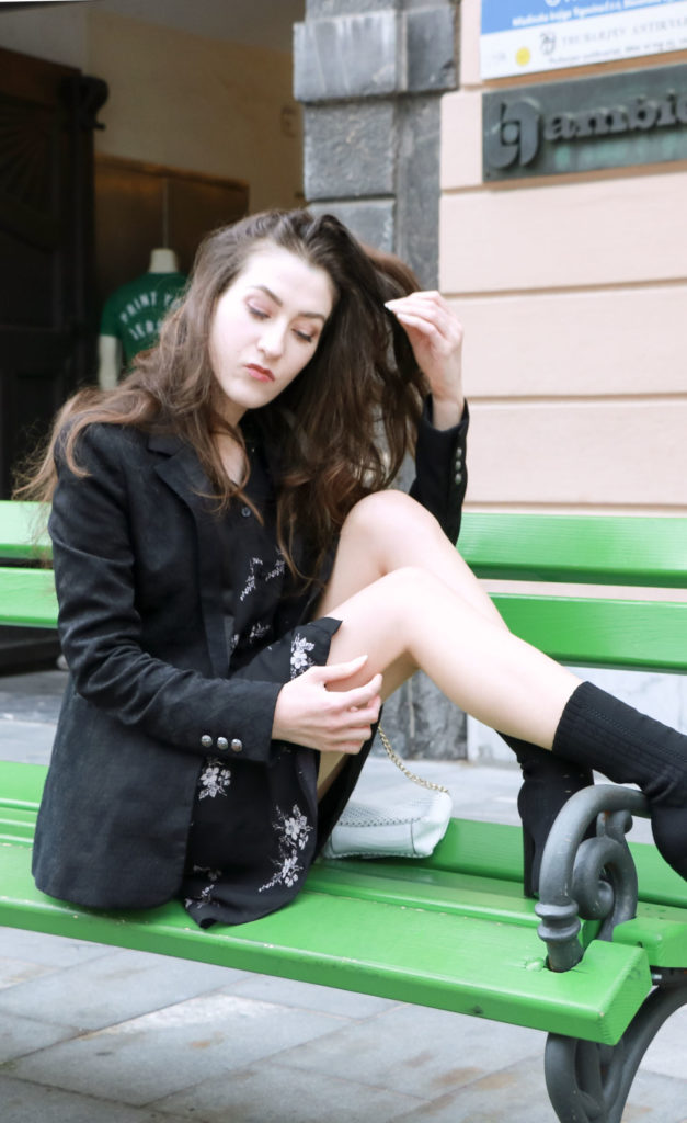 Fashion Blogger Veronika Lipar of Brunette from Wall wearing dark floral shirt dress, black jacquard boyfriend blazer, black sock booties, white shoulder bag sitting on a bench