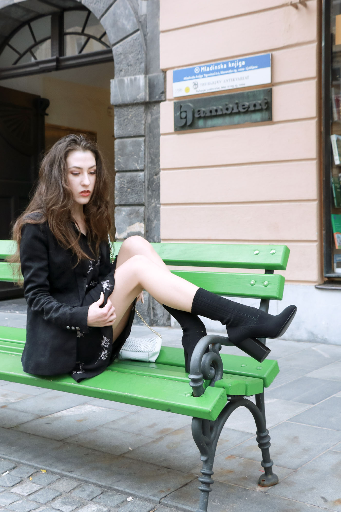 Fashion Blogger Veronika Lipar of Brunette from Wall wearing dark floral shirt dress, black jacquard boyfriend blazer, black sock ankle boots, white shoulder bag, sitting on a bench