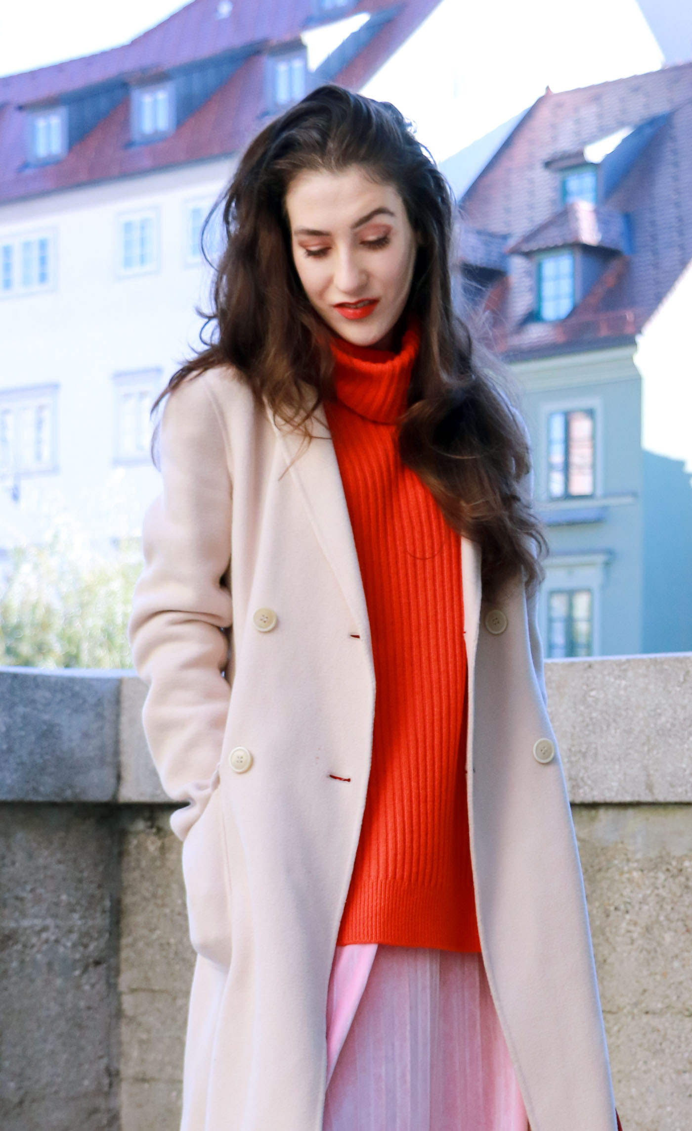 Fashion Blogger Veronika Lipar of Brunette from Wall on the street in pink pleated velvet midi skirt, red oversized Ganni sweater, double breasted Weekend Maxmara coat