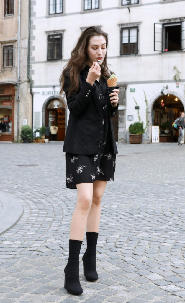 Fashion Blogger Veronika Lipar of Brunette from Wall dressed in dark floral shirt dress, black jacquard boyfriend blazer, black sock ankle boots, white shoulder bag eating ice cream on the street
