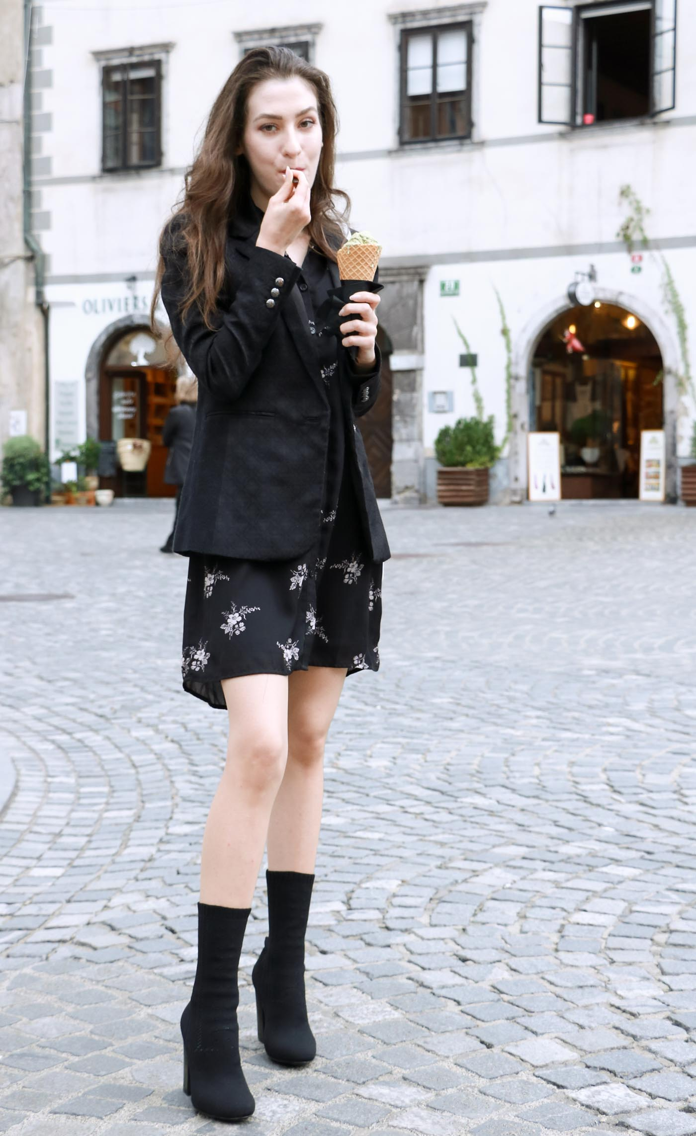 Fashion Blogger Veronika Lipar of Brunette from Wall dressed in decadent floral shirt dress, black jacquard boyfriend blazer, black sock ankle boots, white shoulder bag eating ice cream on the street