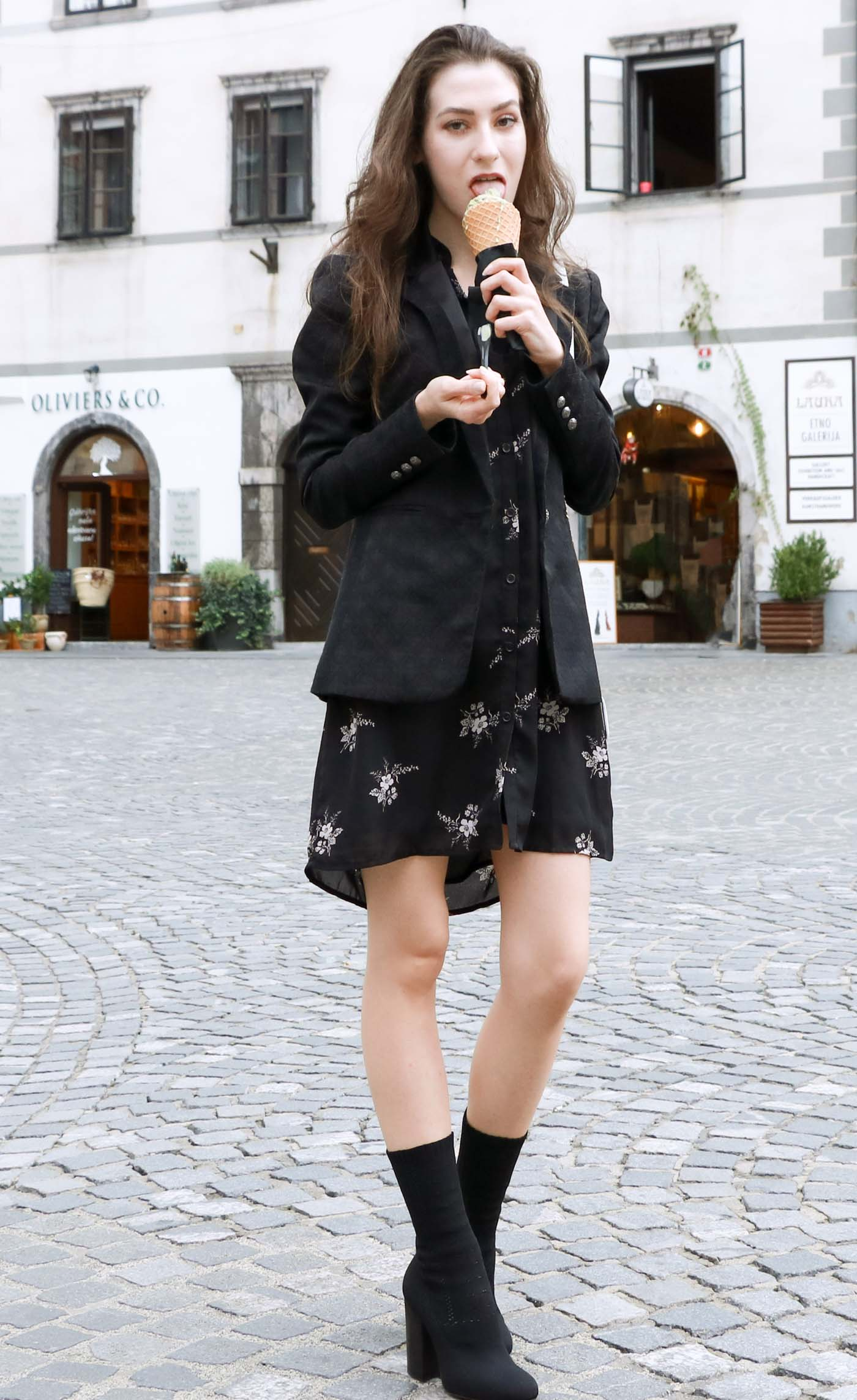 Fashion Blogger Veronika Lipar of Brunette from Wall wearing dark floral shirt dress, black jacquard boyfriend blazer, black sock ankle boots, white shoulder bag, eating ice cream on the street