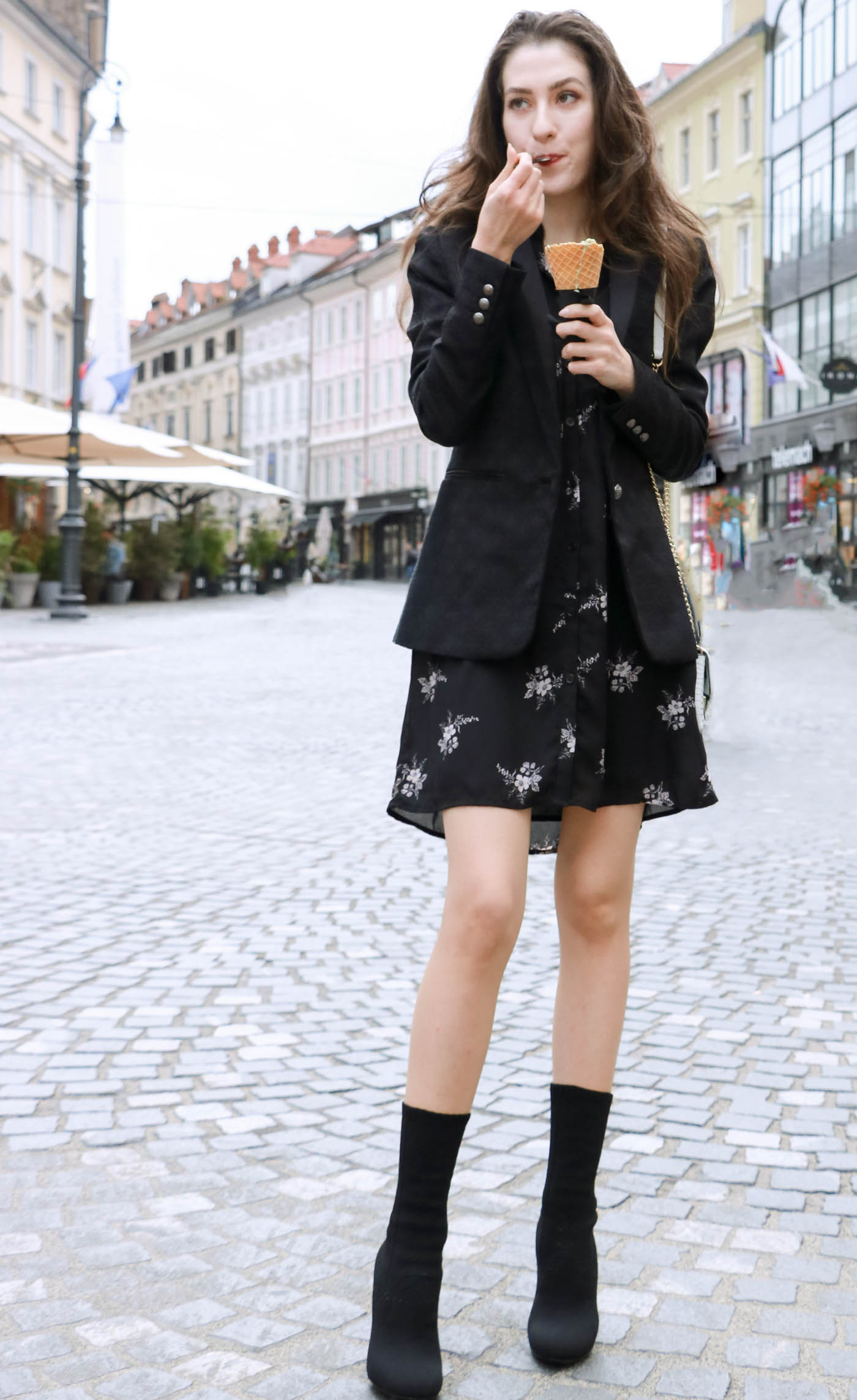 Fashion Blogger Veronika Lipar of Brunette from Wall wearing decadent floral shirt dress, black jacquard boyfriend blazer, black sock booties, white shoulder bag eating ice cream on the street
