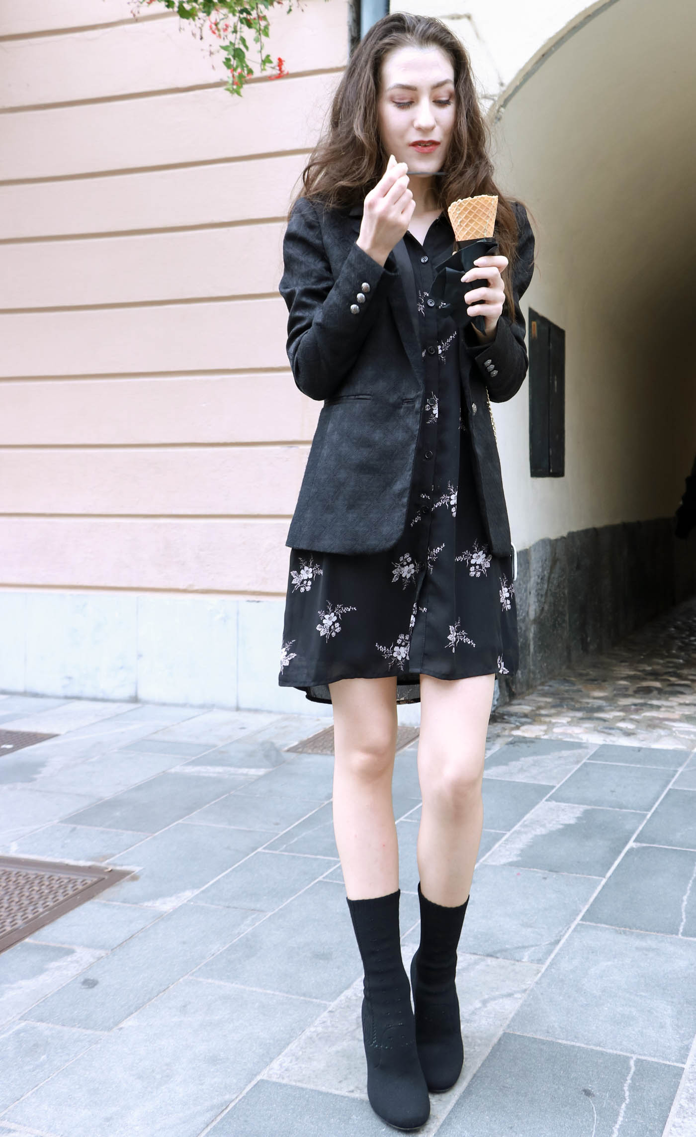 Fashion Blogger Veronika Lipar of Brunette from Wall wearing dark floral shirt dress, black jacquard boyfriend blazer, black sock booties, white shoulder bag eating ice cream on the street