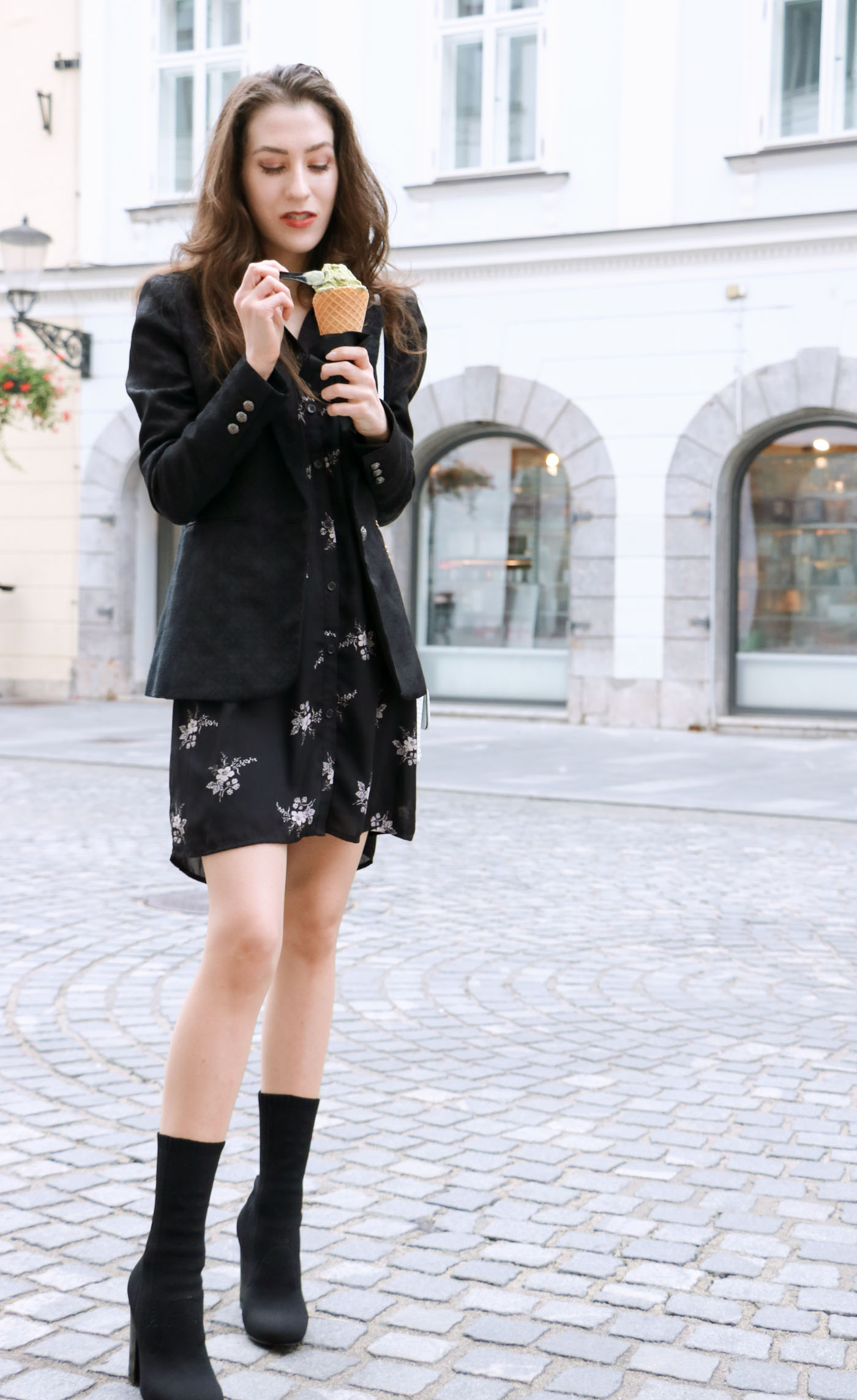 Fashion Blogger Veronika Lipar of Brunette from Wall dressed in dark floral shirt dress, black jacquard boyfriend blazer, black sock booties, white shoulder bag eating ice cream on the street