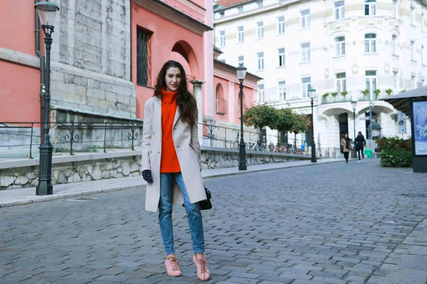 Fashion Blogger Veronika Lipar of Brunette from Wall wearing red Ganni turtleneck sweater, light blue jeans, dusty pink sneakers and Weekend Maxmara beige princess coat