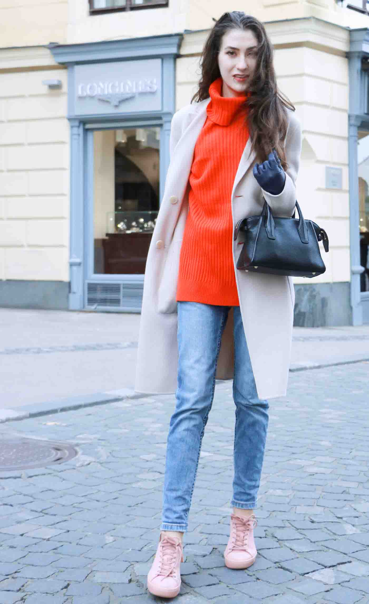 Fashion Blogger Veronika Lipar of Brunette from Wall dressed in red Ganni turtleneck sweater, light blue jeans, pink Puma sneakers and Weekend Maxmara white princess coat