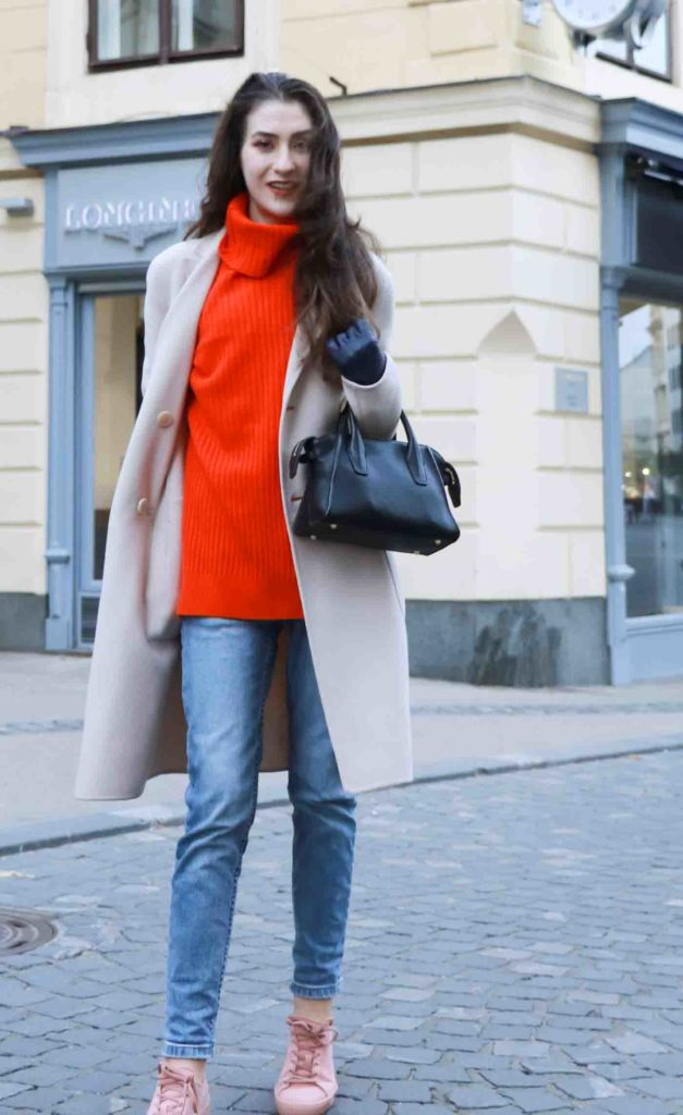 Fashion Blogger Veronika Lipar of Brunette from Wall dressed in red Ganni turtleneck sweater, light blue jeans, pink Puma sneakers and Weekend Maxmara beige princess coat