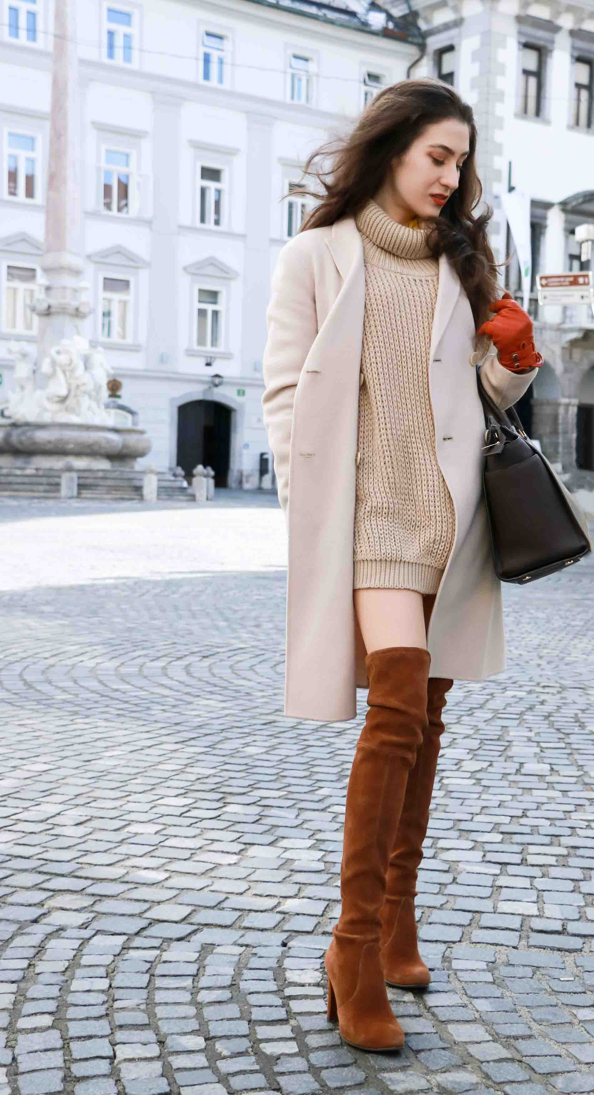 Fashion Blogger Veronika Lipar of Brunette from Wall wearing double breasted coat, cable knit turtleneck camel sweater dress and Stuart Weitzman Highland boots, brown Michael Kors Selma bag, leather gloves
