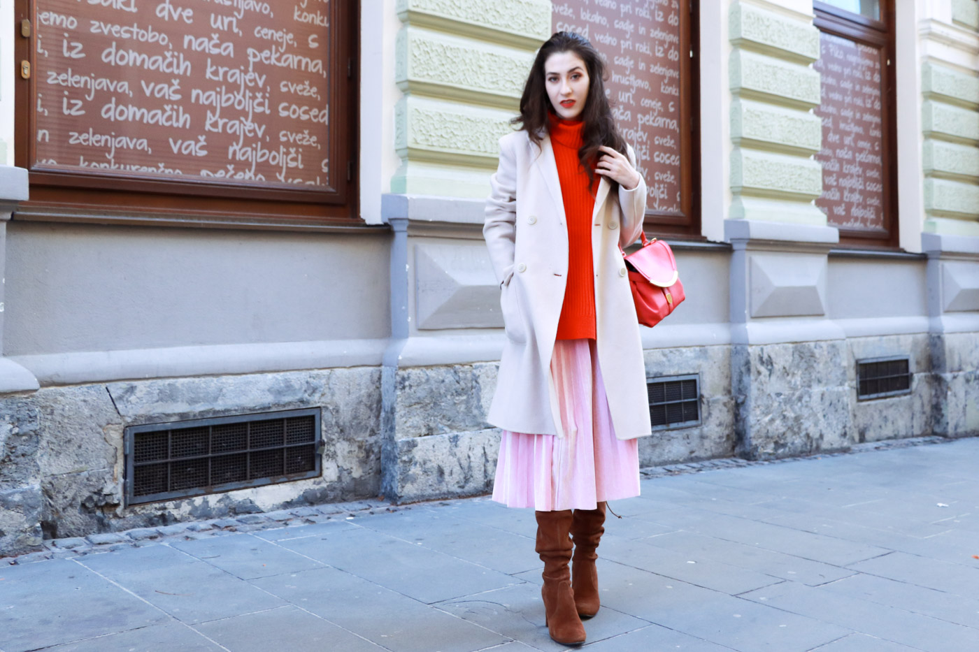 Fashion Blogger Veronika Lipar of Brunette from Wall wearing pink pleated velvet midi skirt, red oversized Ganni sweater, double breasted Weekend Maxmara coat, brown slouchy boots
