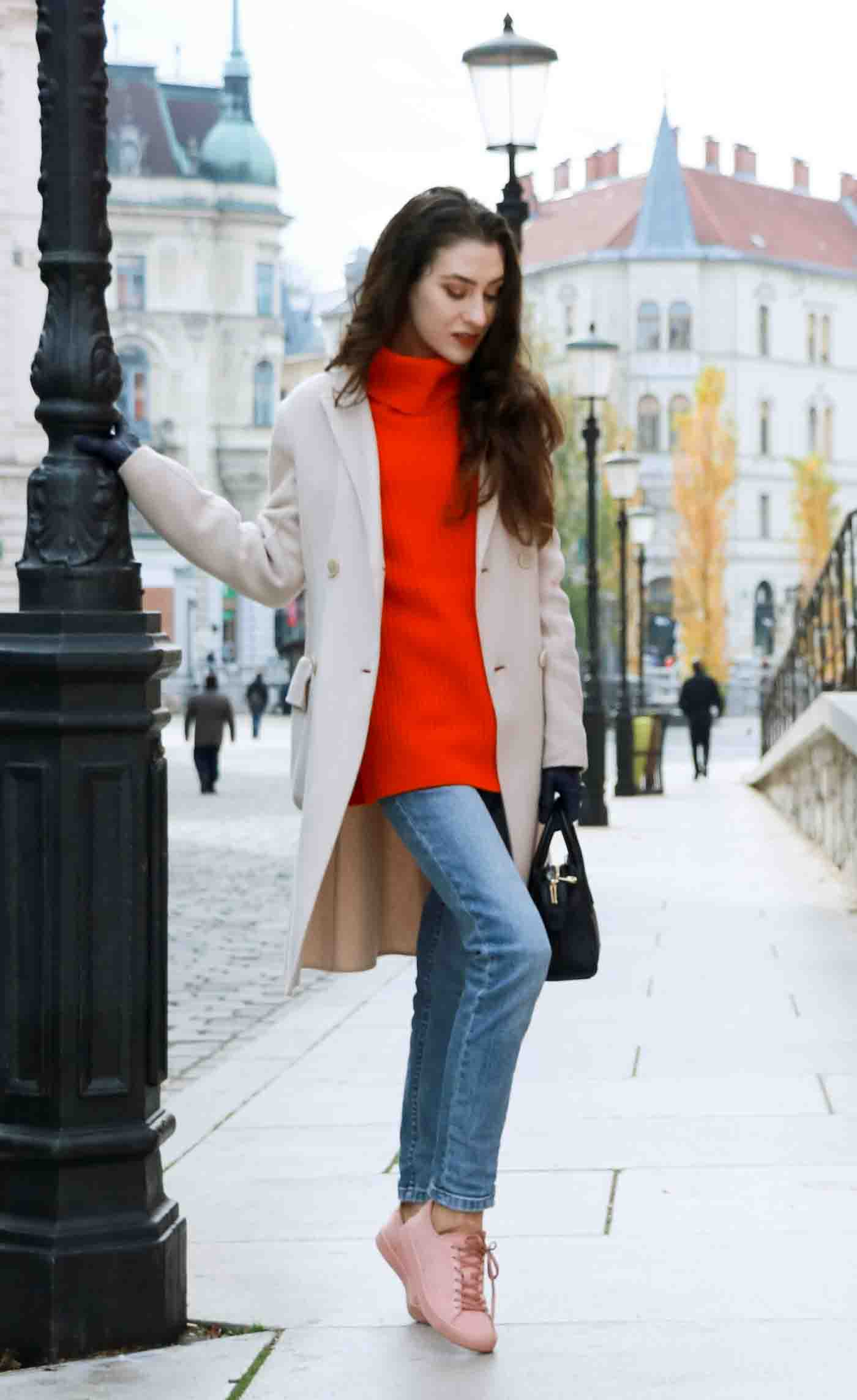 Fashion Blogger Veronika Lipar of Brunette from Wall dressed in red Ganni turtleneck sweater, light blue jeans, pink Puma sneakers and Weekend Max Mara white princess coat