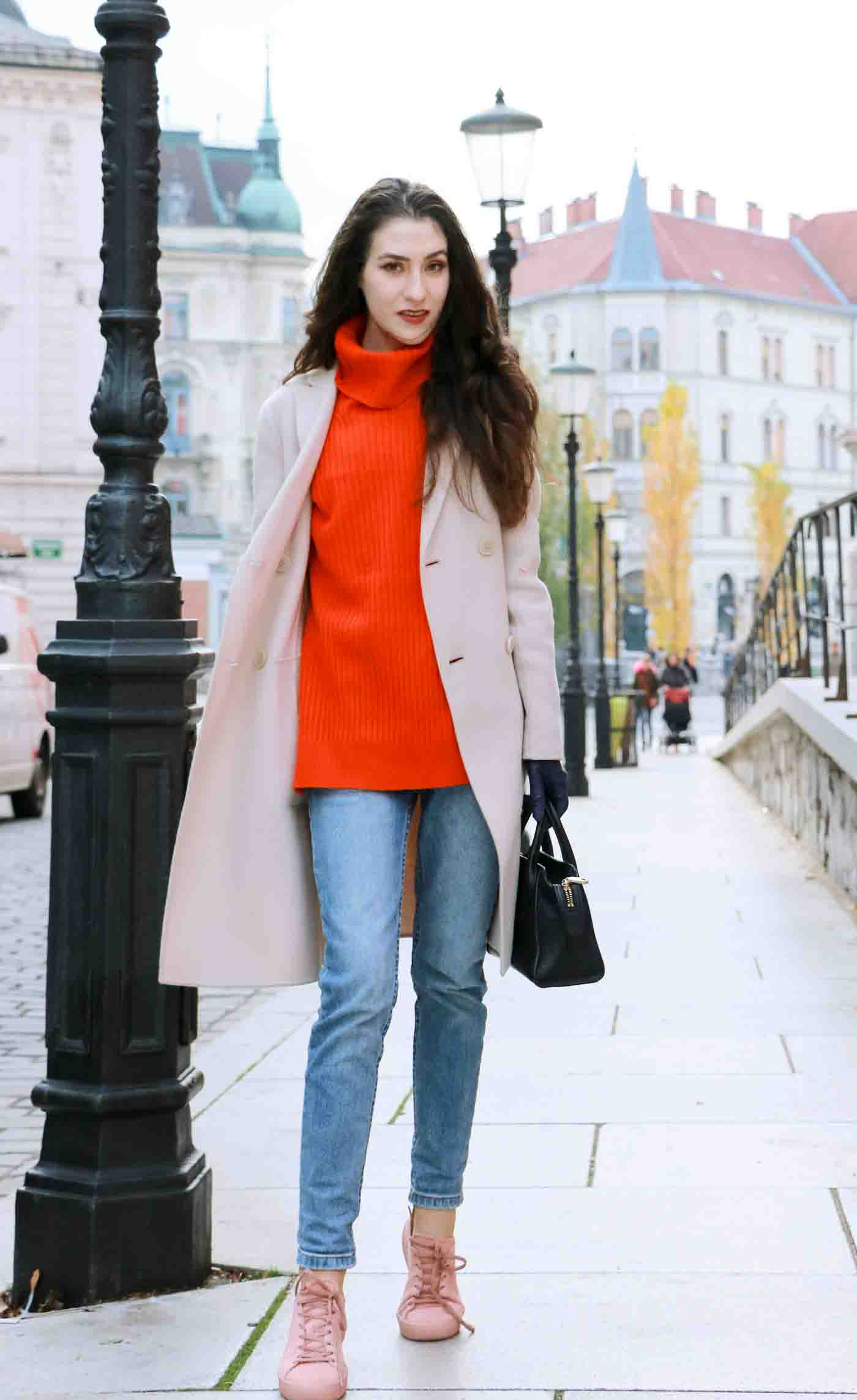 Fashion Blogger Veronika Lipar of Brunette from Wall wearing red Ganni turtleneck sweater, light blue jeans, pink Puma sneakers and Weekend Maxmara beige princess coat