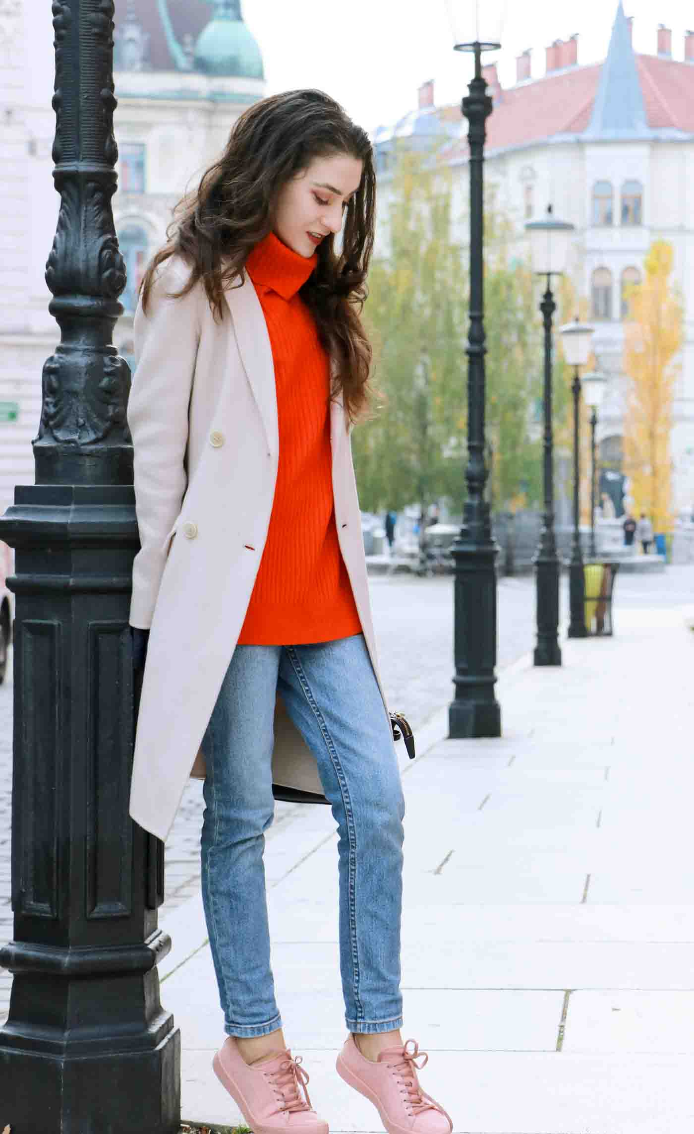 Fashion Blogger Veronika Lipar of Brunette from Wall wearing red Ganni turtleneck sweater, light blue jeans, pink Puma sneakers and Weekend Maxmara white princess coat