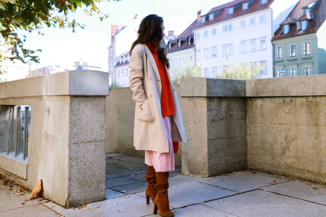 walking around in pink pleated velvet midi skirt, red oversized Ganni sweater, double breasted Weekend Maxmara coat, brown Stuart Weitzman boots