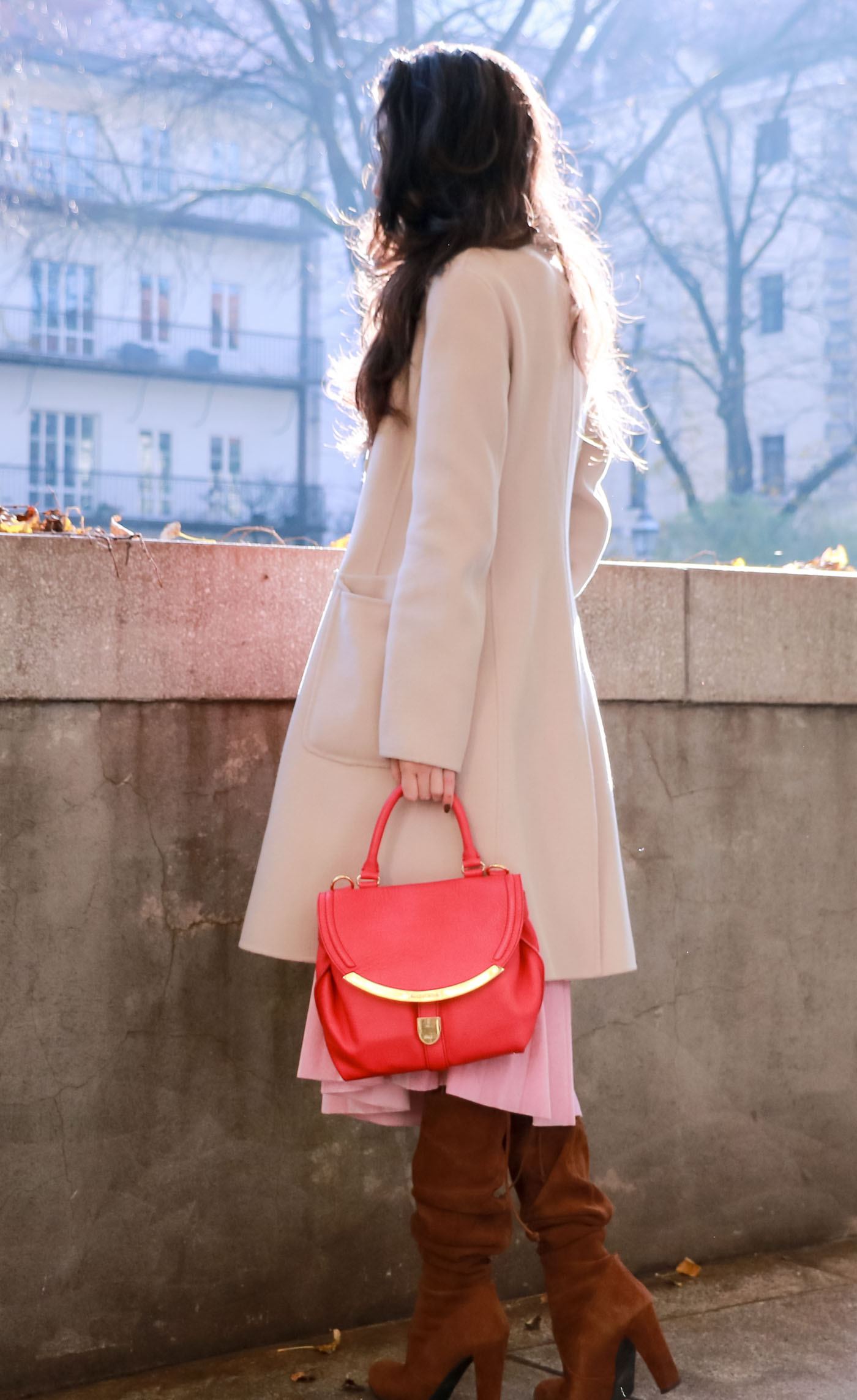 Fashion Blogger Veronika Lipar of Brunette from Wall on the street in pink pleated velvet midi skirt, red oversized Ganni sweater, double breasted Weekend Maxmara coat, brown slouchy boots