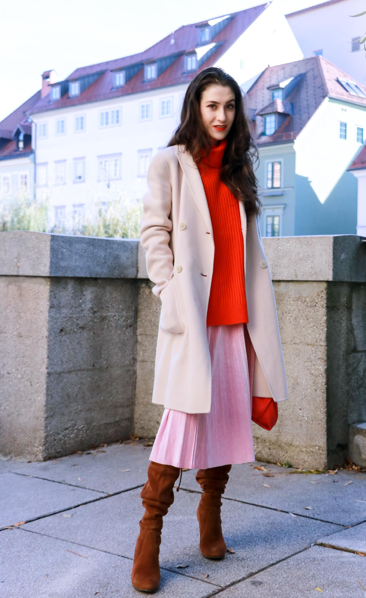 Fashion Blogger Veronika Lipar of Brunette from Wall walking around in pink pleated velvet midi skirt, red oversized Ganni sweater, double breasted Weekend Maxmara coat, brown Stuart Weitzman boots