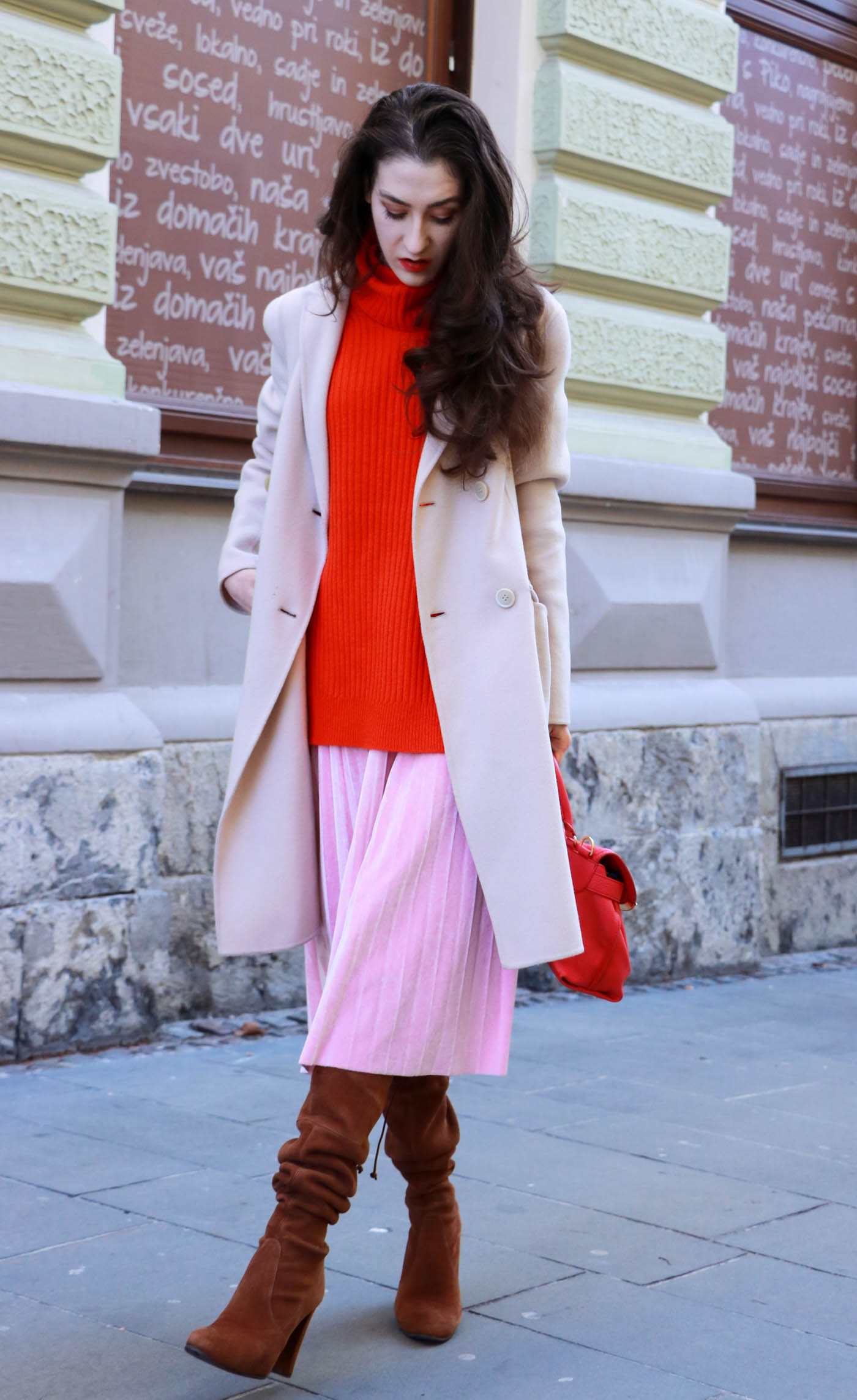Fashion Blogger Veronika Lipar of Brunette from Wall dressed in pink pleated velvet midi skirt, red oversized Ganni sweater, double breasted Weekend Maxmara coat, brown Stuart Weitzman boots