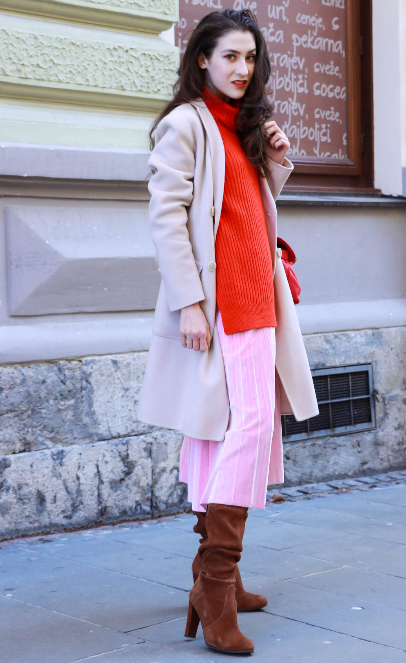 Fashion Blogger Veronika Lipar of Brunette from Wall wearing pink pleated velvet midi skirt, red oversized Ganni sweater, double breasted Weekend Maxmara coat, brown Stuart Weitzman boots