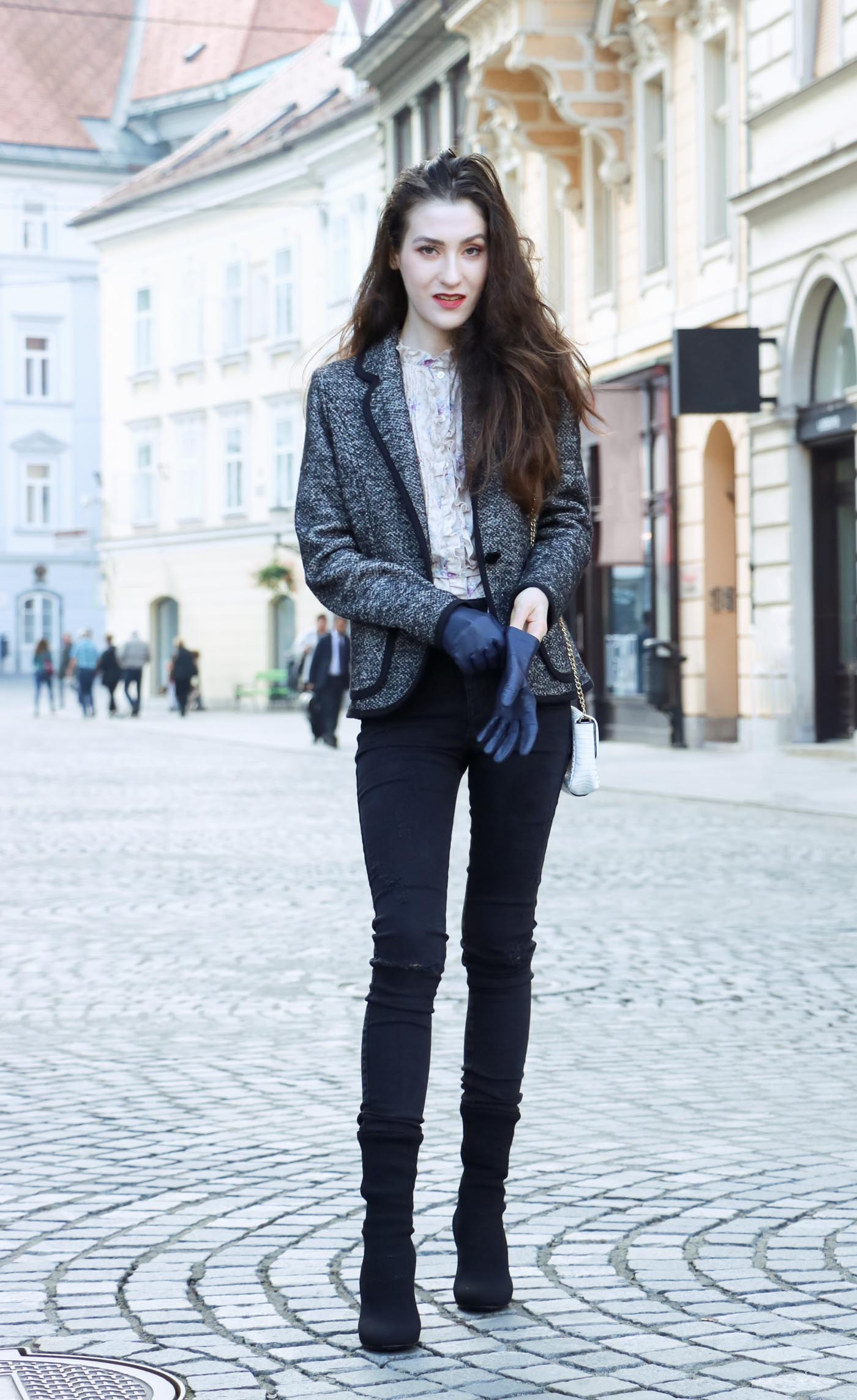 Fashion Blogger Veronika Lipar of Brunette from Wall wearing black skinny jeans, black sock ankle boots and floral high collar blouse under tweed black and white blazer