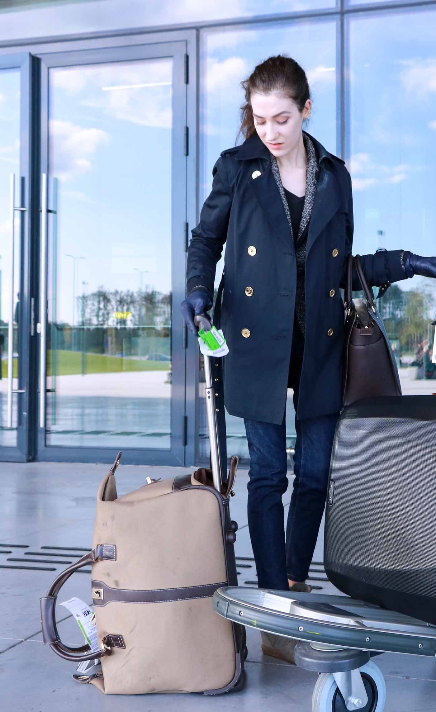 Fashion Blogger Veronika Lipar of Brunette from Wall Street wearing trench coat, jeans and Michael Kors Selma Bag tote at the airport