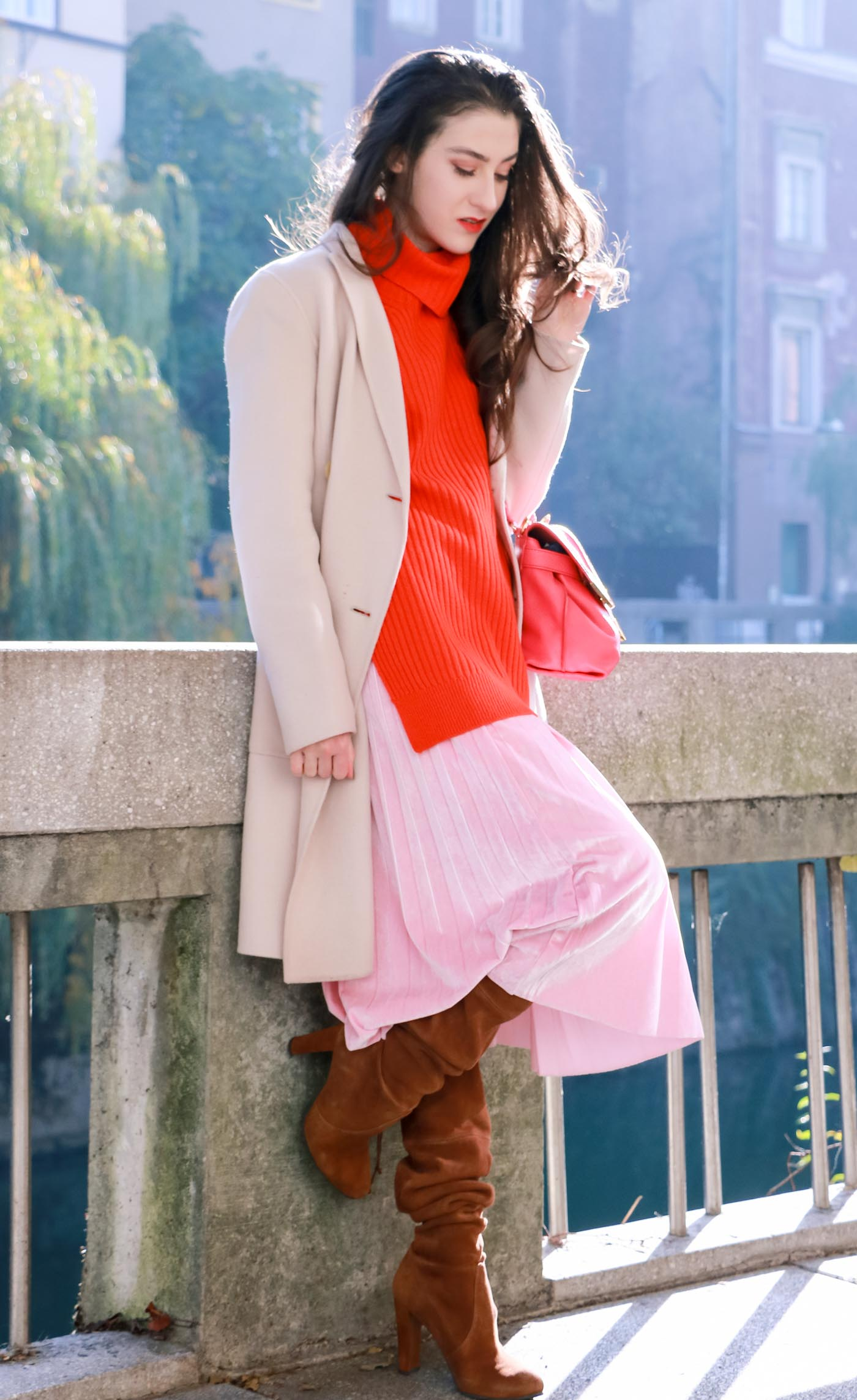 Fashion Blogger Veronika Lipar of Brunette from Wall dressed in pink pleated velvet midi skirt, red oversized Ganni sweater, double breasted Weekend Maxmara coat, brown slouchy boots