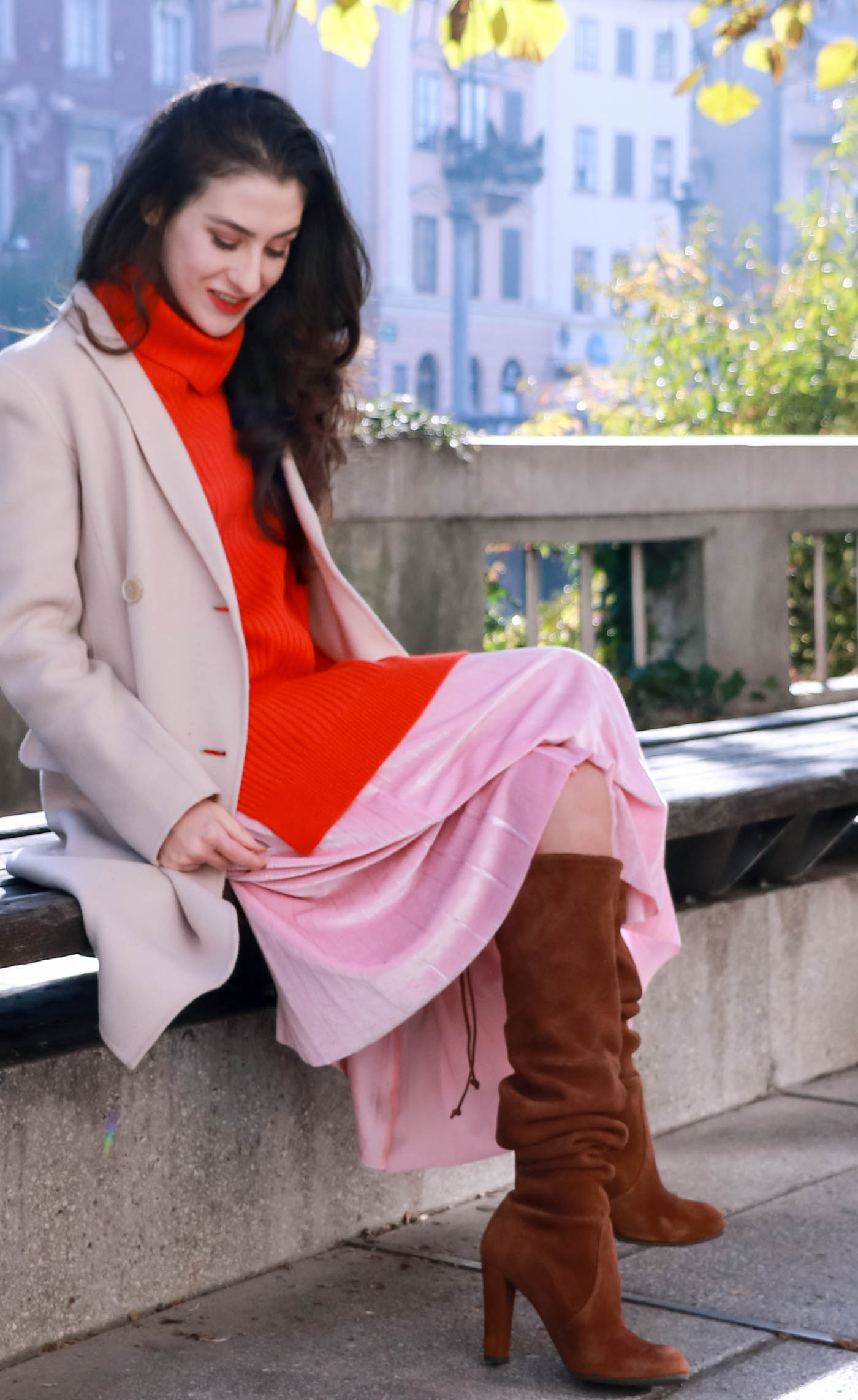 Fashion Blogger Veronika Lipar of Brunette from Wall sitting on a bench dressed in pink pleated velvet midi skirt, double breasted Weekend Maxmara coat, brown Stuart Weitzman boots