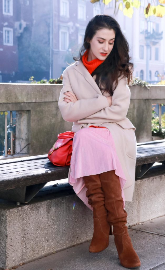 Fashion Blogger Veronika Lipar of Brunette from Wall sitting on a bench wearing pink pleated velvet midi skirt, brown slouchy boots