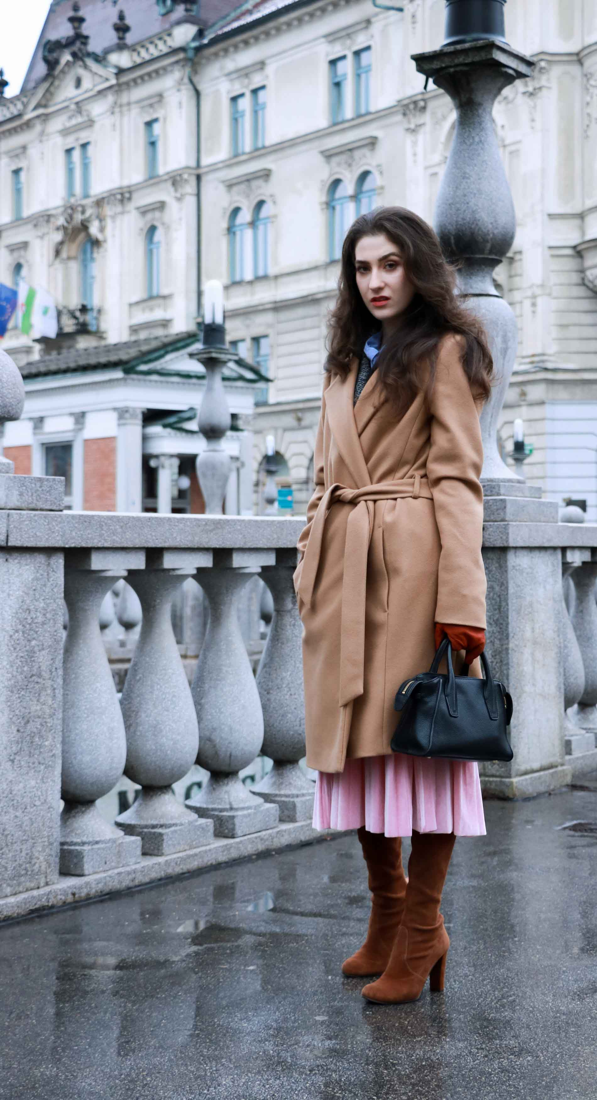 Fashion Blogger Veronika Lipar of Brunette from Wall Street wearing winter outfit, ESCADA wrap camel coat, pink velvet midi pleated skirt, brown Stuart Weitzman Highland OTK boots, black top handle bag, leather gloves, when going to Christmas brunch