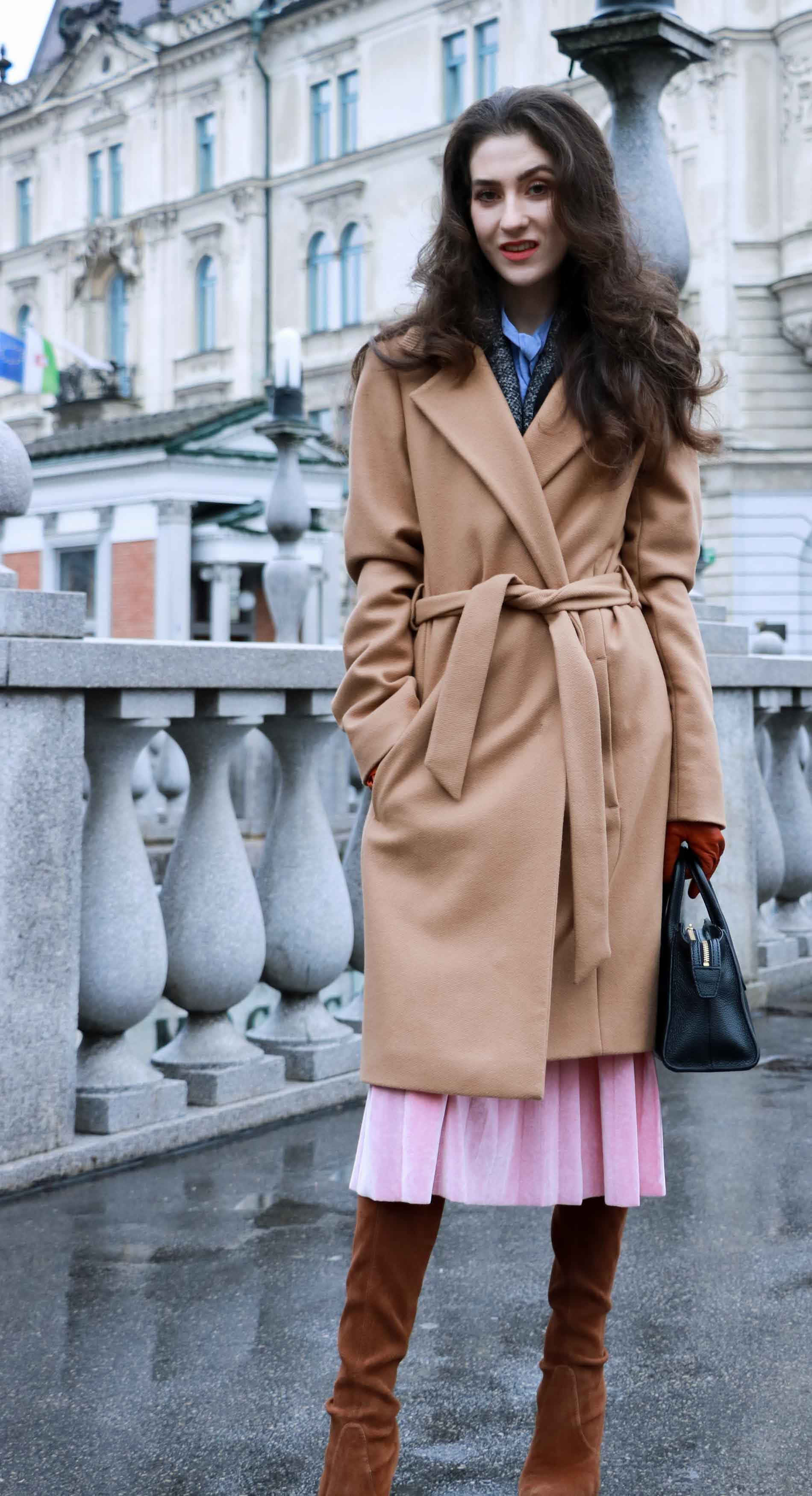 Fashion Blogger Veronika Lipar of Brunette from Wall Street wearing elegant outfit, ESCADA wrap camel coat, pink velvet midi pleated skirt, brown Stuart Weitzman Highland over the knee boots, black top handle bag, leather gloves