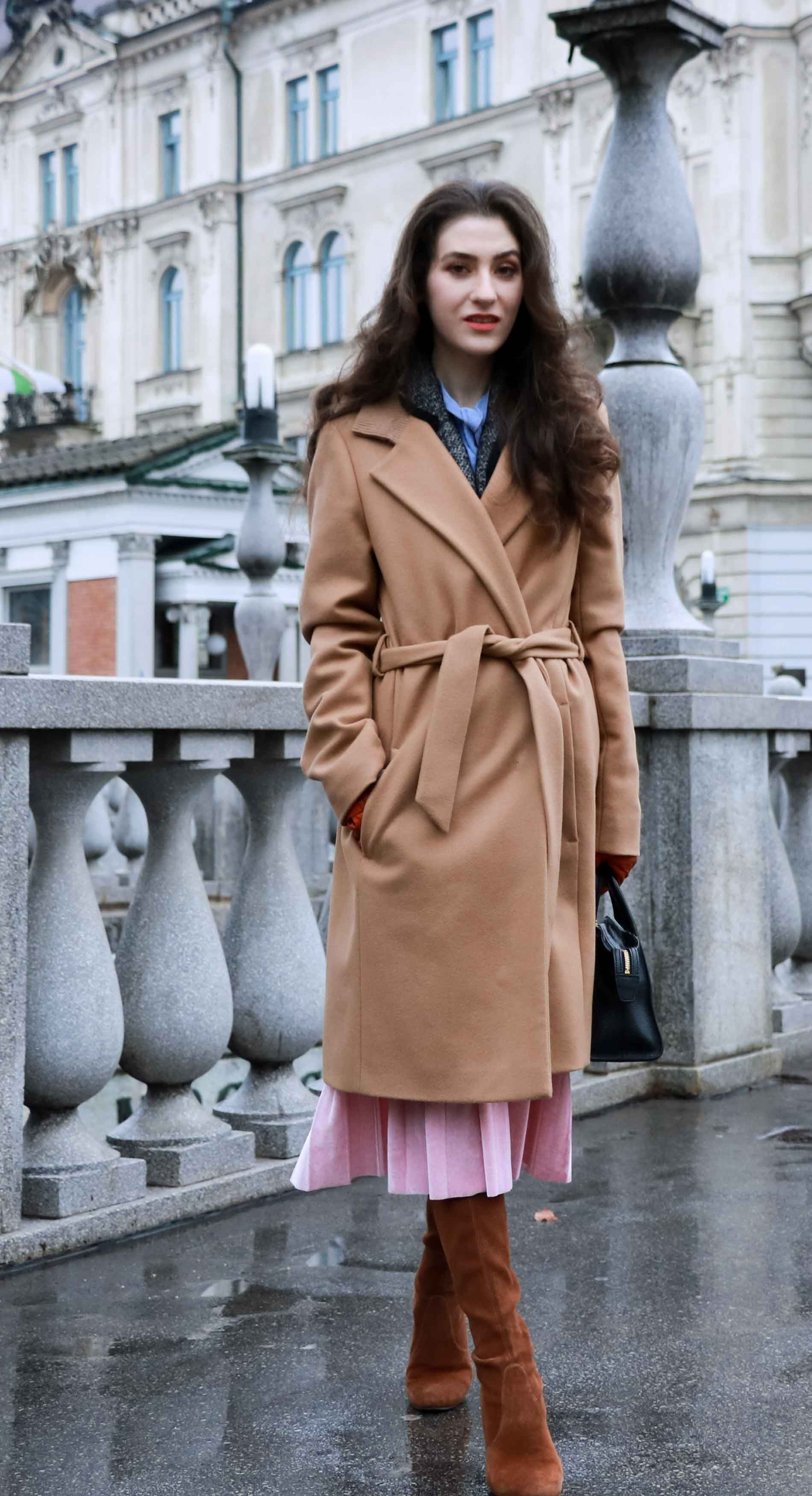 Fashion Blogger Veronika Lipar of Brunette from Wall Street wearing elegant winter outfit, ESCADA wrap camel coat, pink velvet midi pleated skirt, brown Stuart Weitzman Highland over the knee boots, black top handle bag, leather gloves this Christmas
