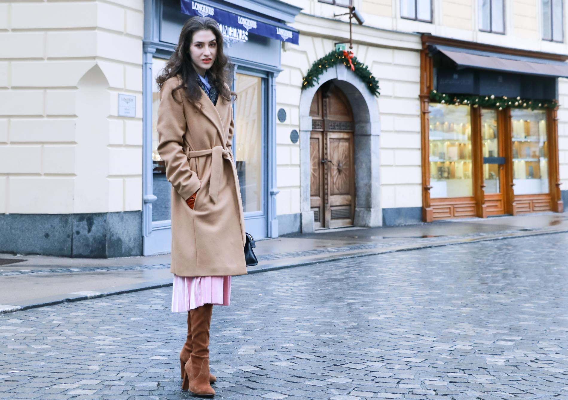 Fashion Blogger Veronika Lipar of Brunette from Wall Street wearing fashionable winter outfit, ESCADA wrap camel coat, pink velvet midi pleated skirt, brown Stuart Weitzman Highland over the knee boots, black top handle bag, leather gloves on the streets of Ljubljana