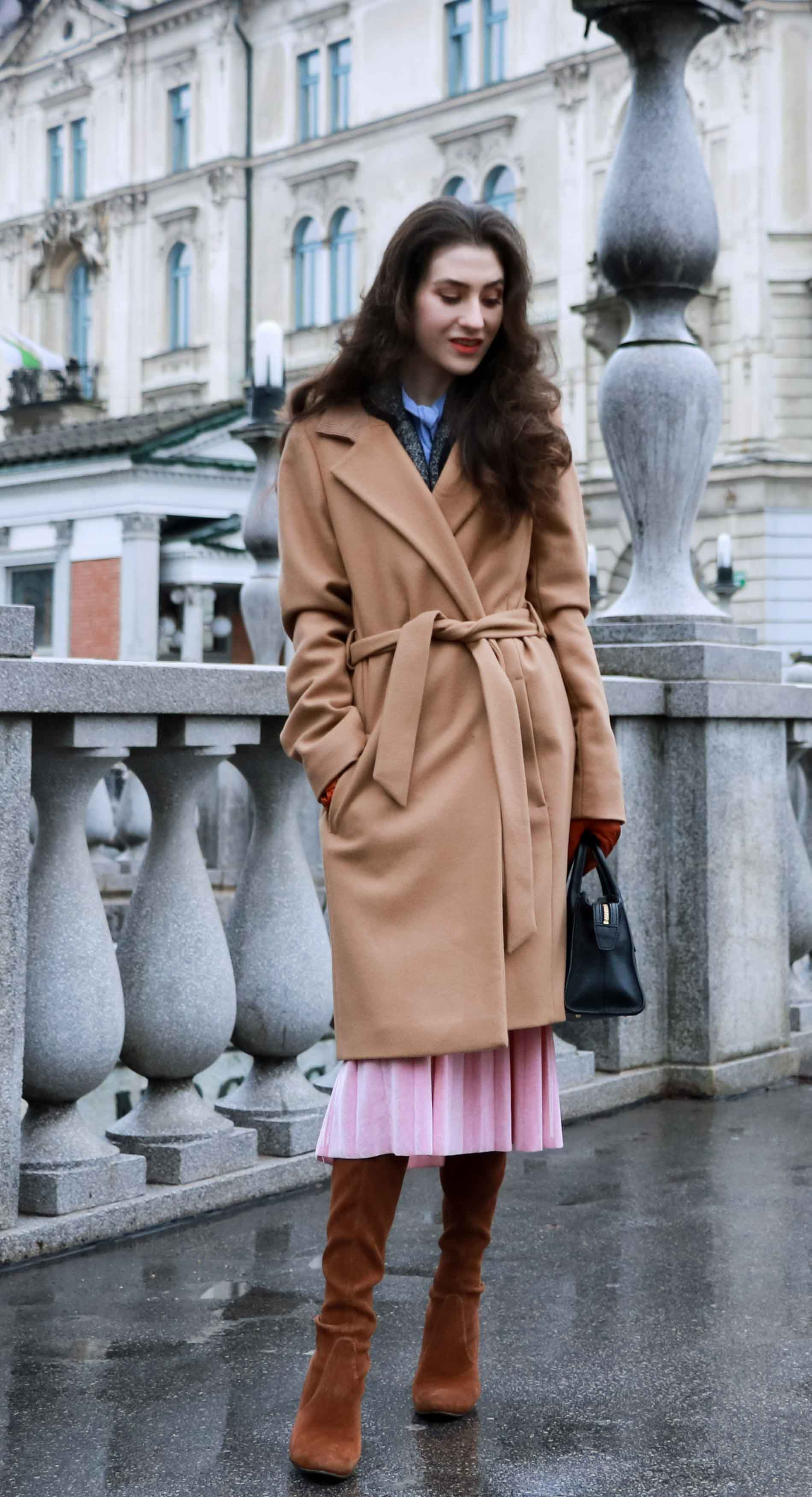 Fashion Blogger Veronika Lipar of Brunette from Wall Street wearing elegant outfit, ESCADA wrap camel coat, pink velvet midi pleated skirt, brown Stuart Weitzman Highland OTK boots, black top handle bag, leather gloves
