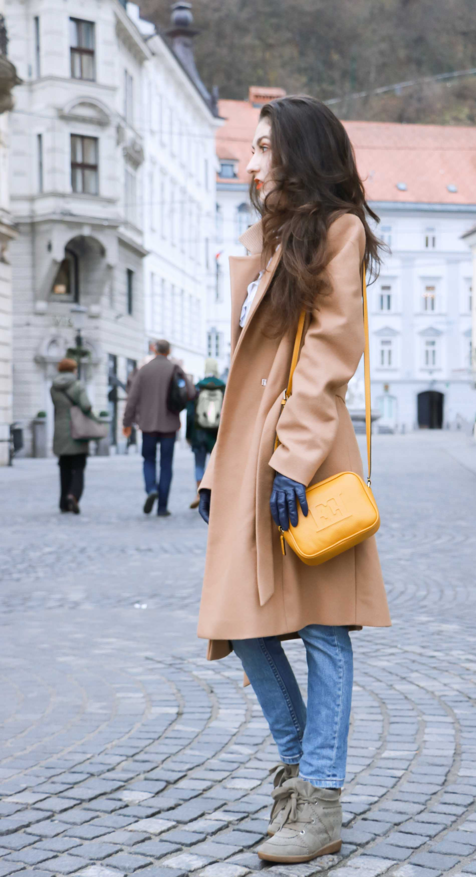 Fashion Blogger Veronika Lipar of Brunette from Wall Street wearing off-duty outfit, ESCADA wrap camel coat, A.P.C. blue jeans, Isabel Marant olive Bobby Sneakers, yellow shoulder bag from Escada, white Victorian blouse
