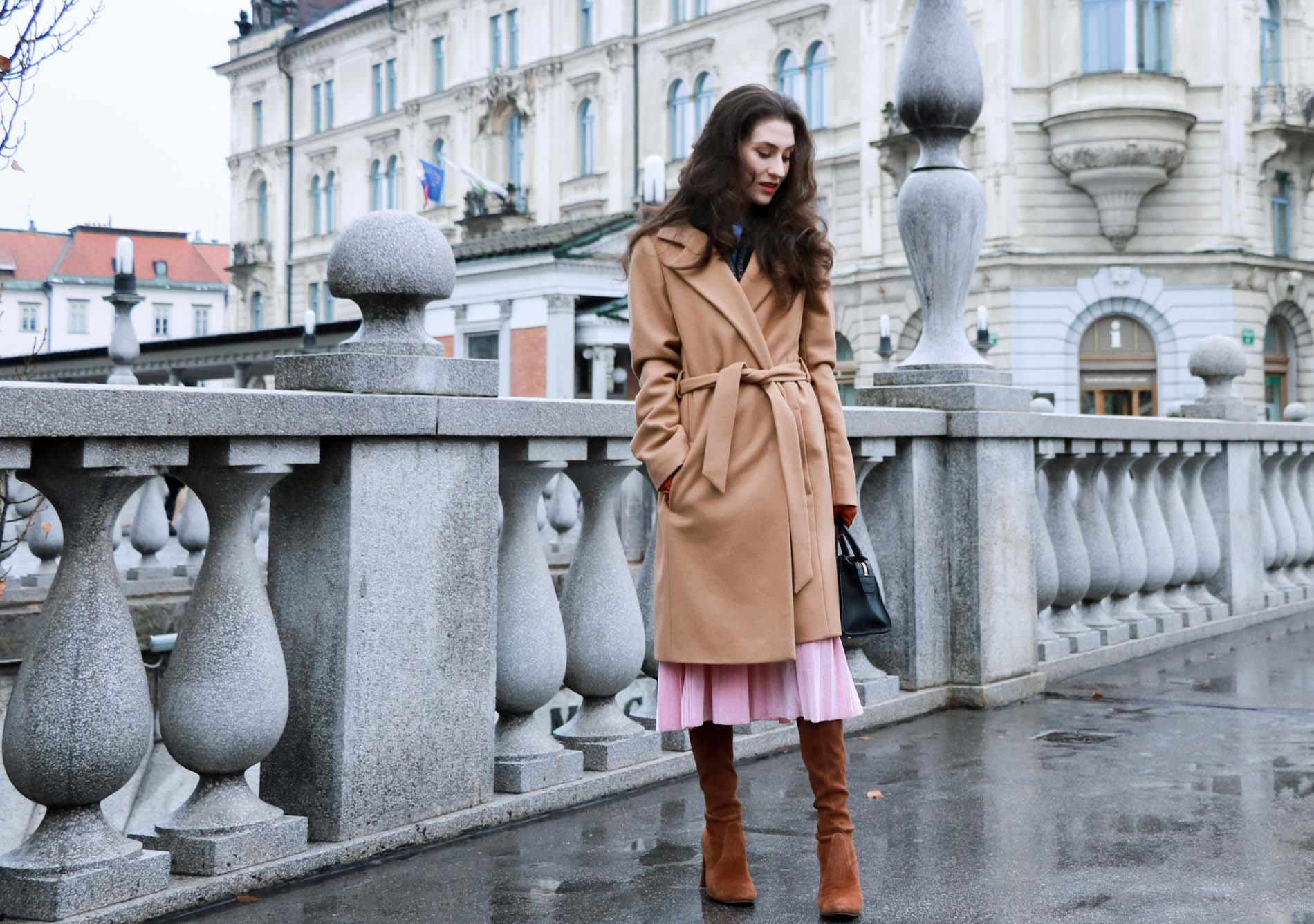 Fashion Blogger Veronika Lipar of Brunette from Wall Street wearing ESCADA wrap camel coat, pink velvet midi pleated skirt, brown Stuart Weitzman Highland over the knee boots, black top handle bag, leather gloves