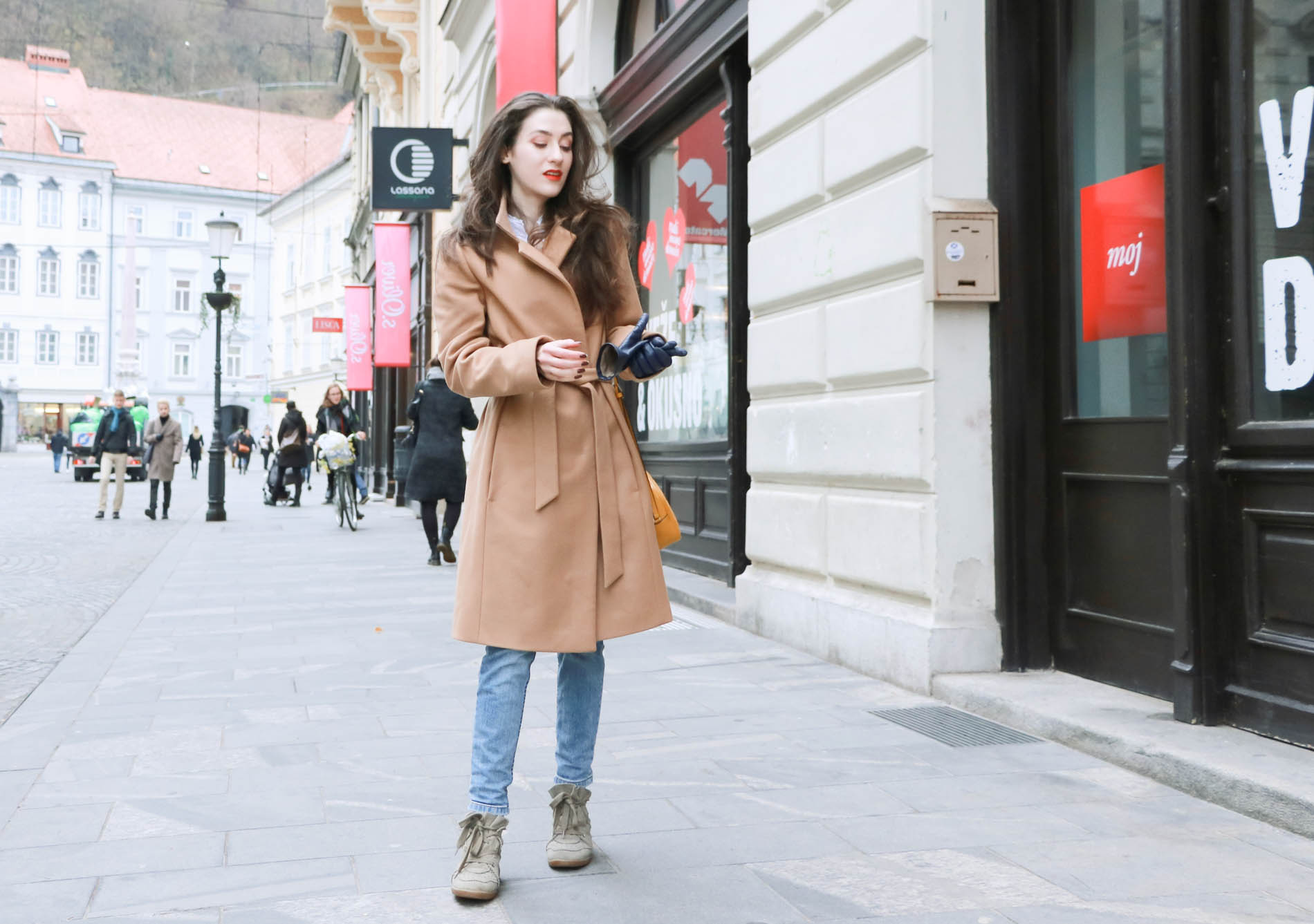 Fashion Blogger Veronika Lipar of Brunette from Wall Street wearing ESCADA wrap camel coat, A.P.C. blue jeans, Isabel Marant olive Bobby Sneakers, yellow shoulder bag from Escada, white Victorian blouse