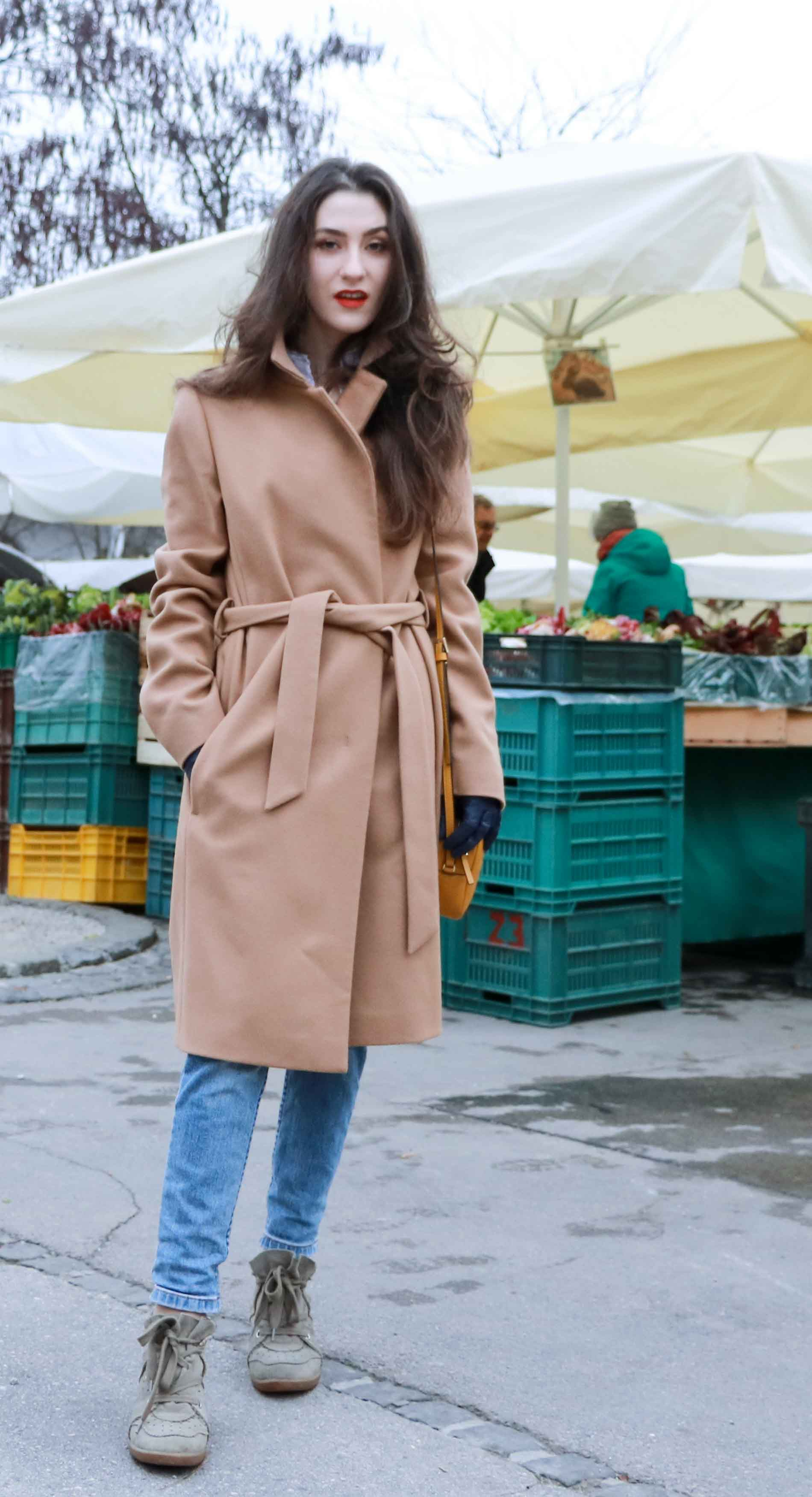 Fashion Blogger Veronika Lipar of Brunette from Wall Street dressed in ESCADA wrap camel coat, A.P.C. blue jeans, Isabel Marant olive Bobby Sneakers, yellow shoulder bag from Escada, white Victorian blouse at the grocery's market