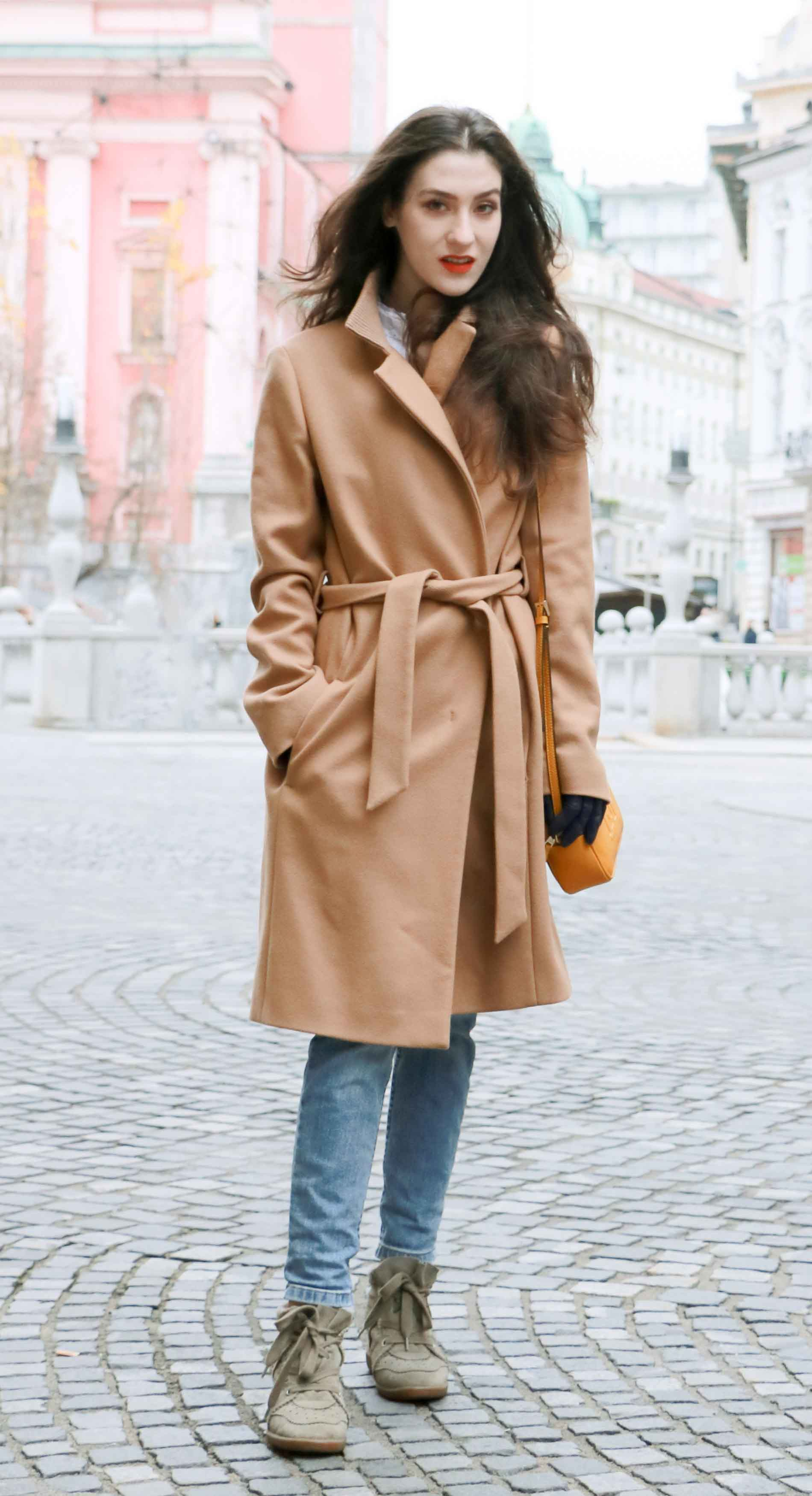 Fashion Blogger Veronika Lipar of Brunette from Wall Street wearing winter outfit, ESCADA wrap camel coat, A.P.C. blue jeans, Isabel Marant olive Bobby Sneakers, yellow shoulder bag from Escada, white Victorian blouse