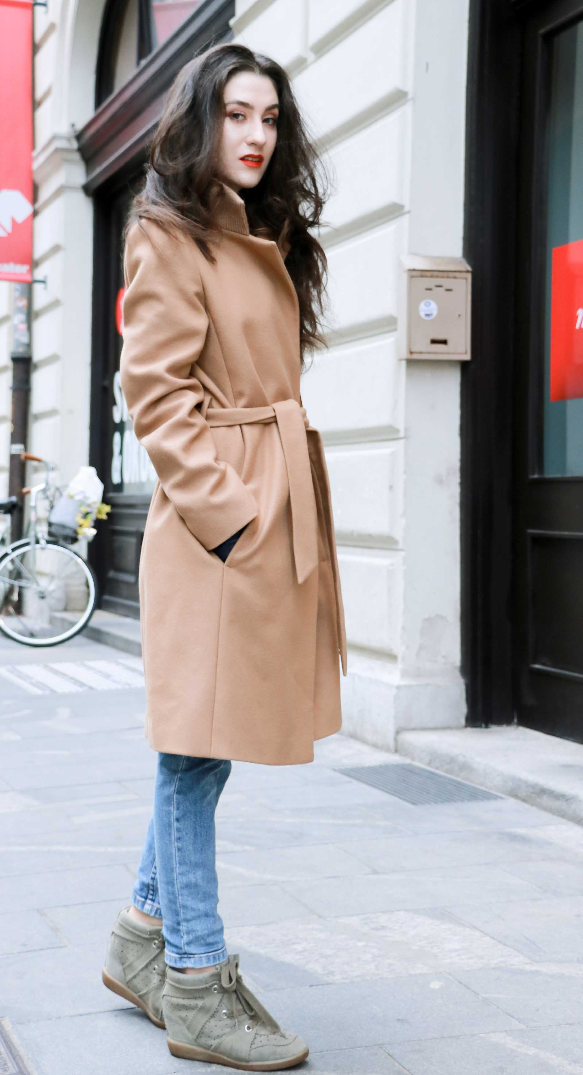 Fashion Blogger Veronika Lipar of Brunette from Wall Street wearing casual outfit, ESCADA wrap camel coat, A.P.C. blue jeans, Isabel Marant olive Bobby Sneakers, yellow shoulder bag from Escada, white Victorian blouse
