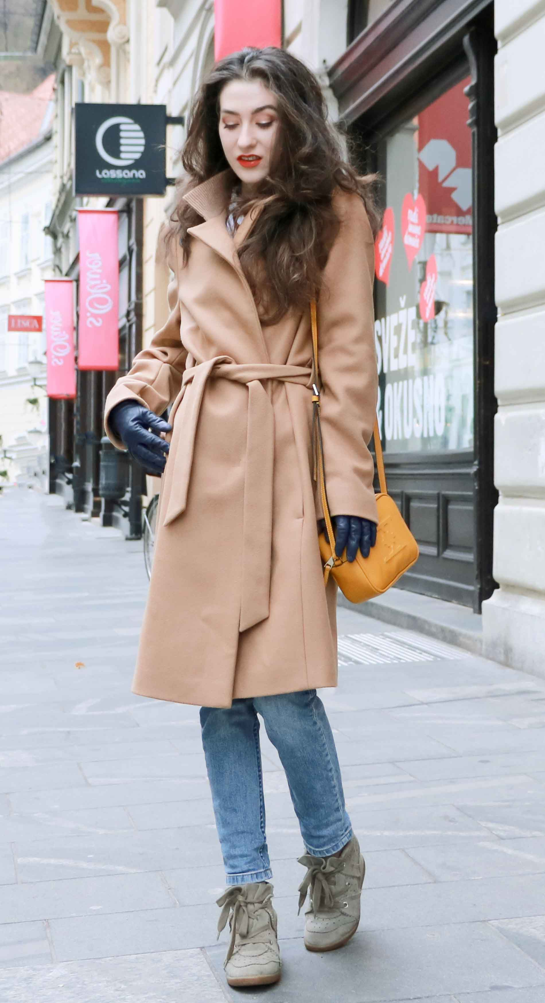 Fashion Blogger Veronika Lipar of Brunette from Wall Street dressed casual outfit, ESCADA wrap camel coat, A.P.C. blue jeans, Isabel Marant olive Bobby Sneakers, yellow shoulder bag from Escada, white Victorian blouse on the streets of Ljubljana